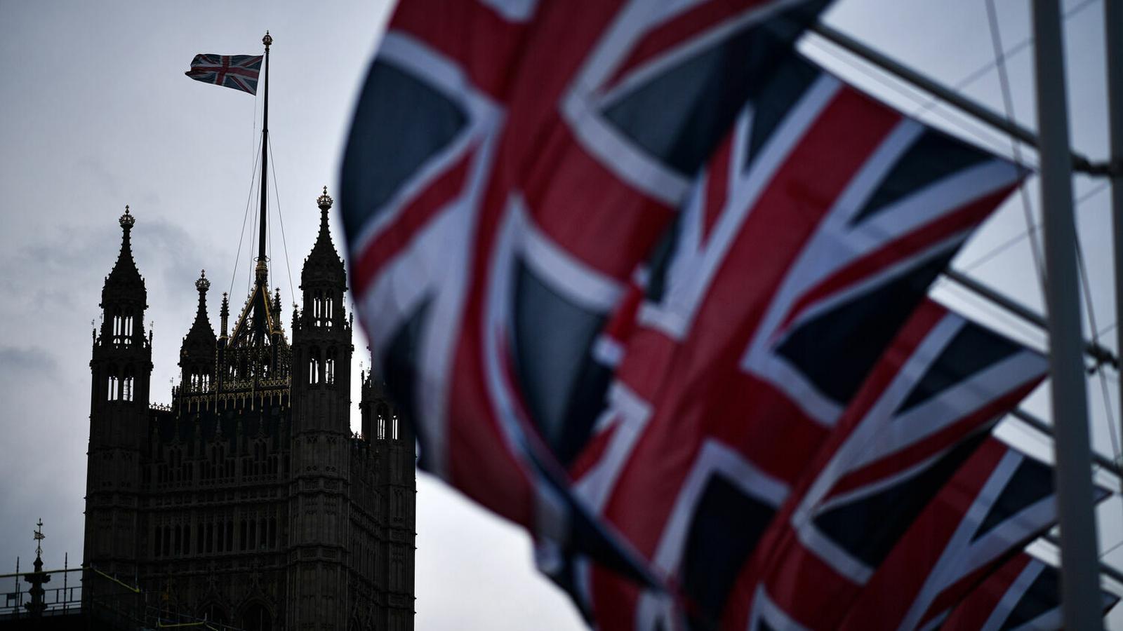 La Union Jack en primer terme, sobre una de les torres del palau de Westminster al fons. / DANIEL LEAL-OLIVAS (EFE)