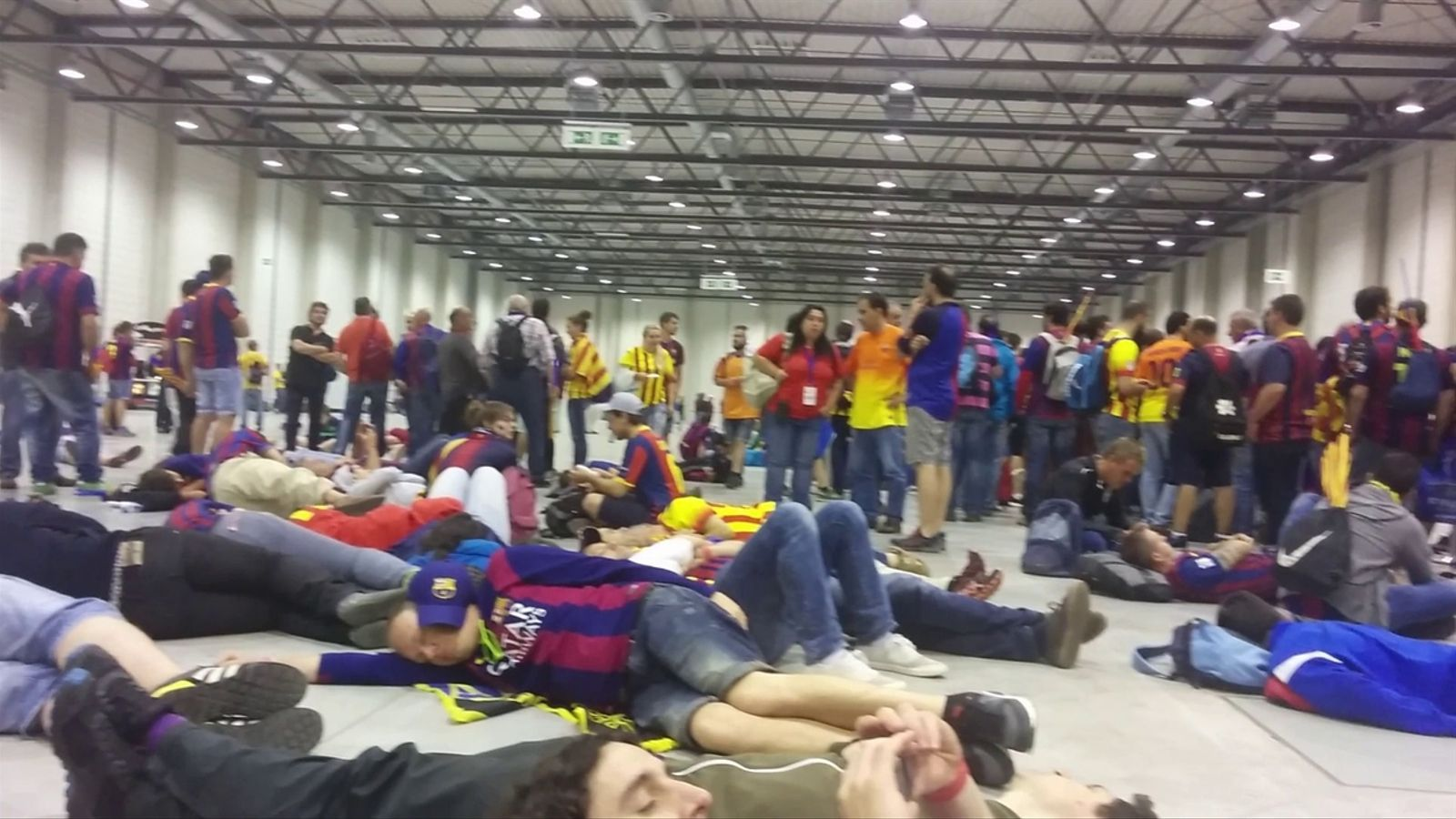Aficionats del Barça, dormint pel terra esperant els vols de tornada