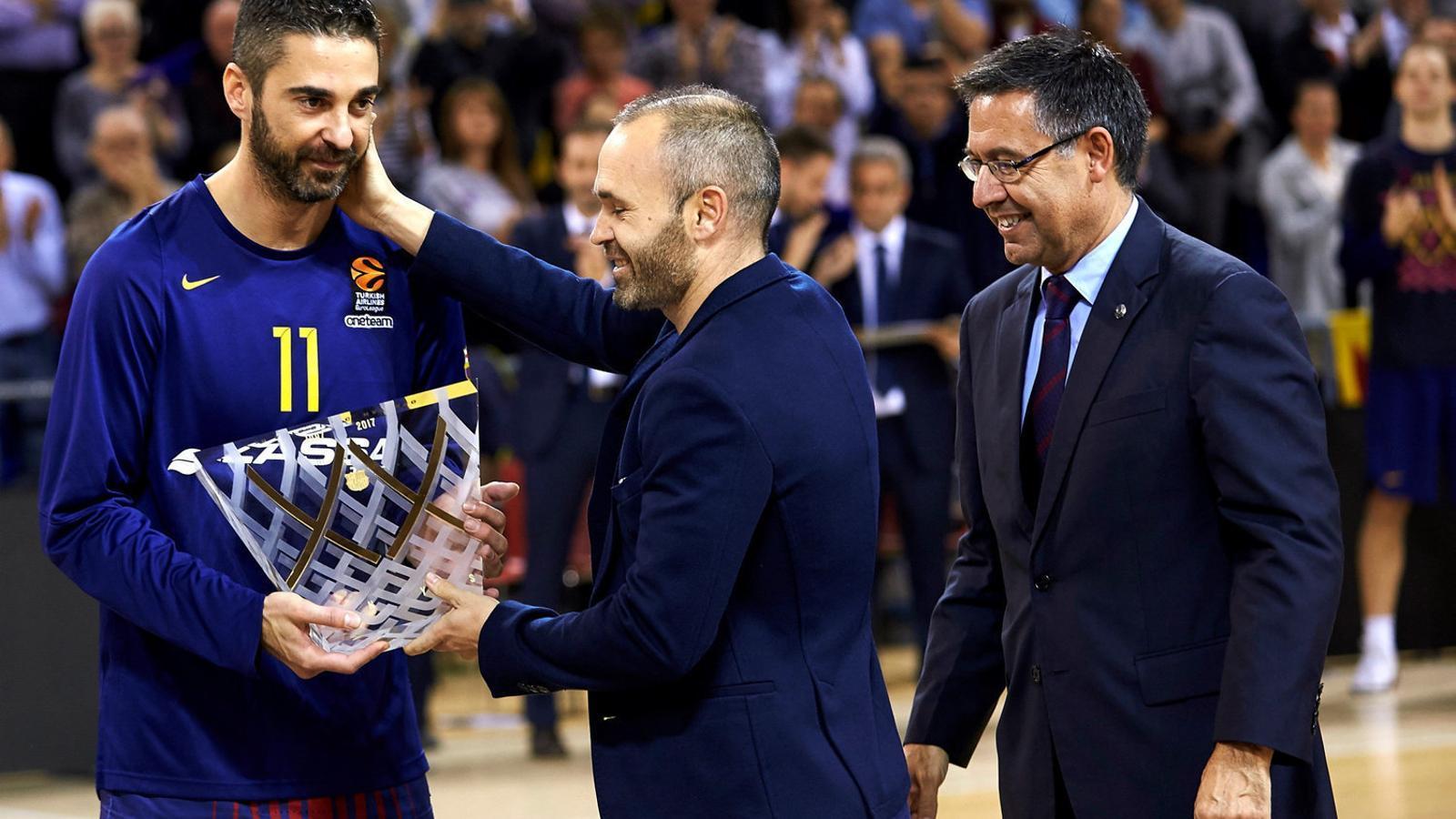 Joan Carles Navarro, capità del Barça Lassa, rebent un trofeu de mans d'Andrés Iniesta durant l'homenatge previ al partit.