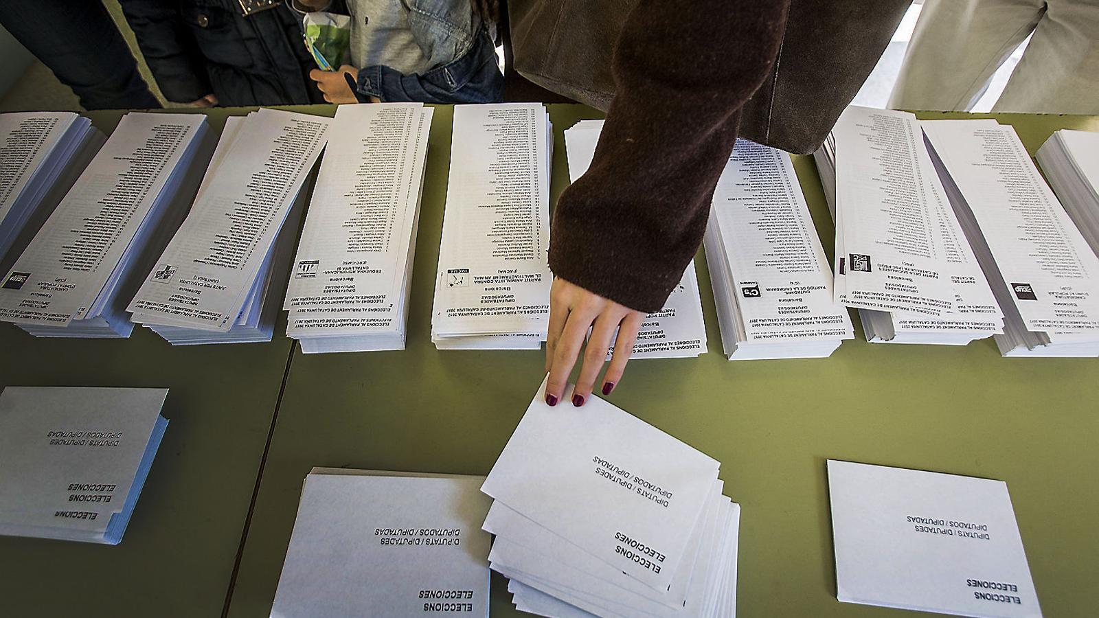 Una persona en un col·legi electoral escollint una de les paperetes dels partits polítics que es van presentar a les eleccions del 21 de desembre.