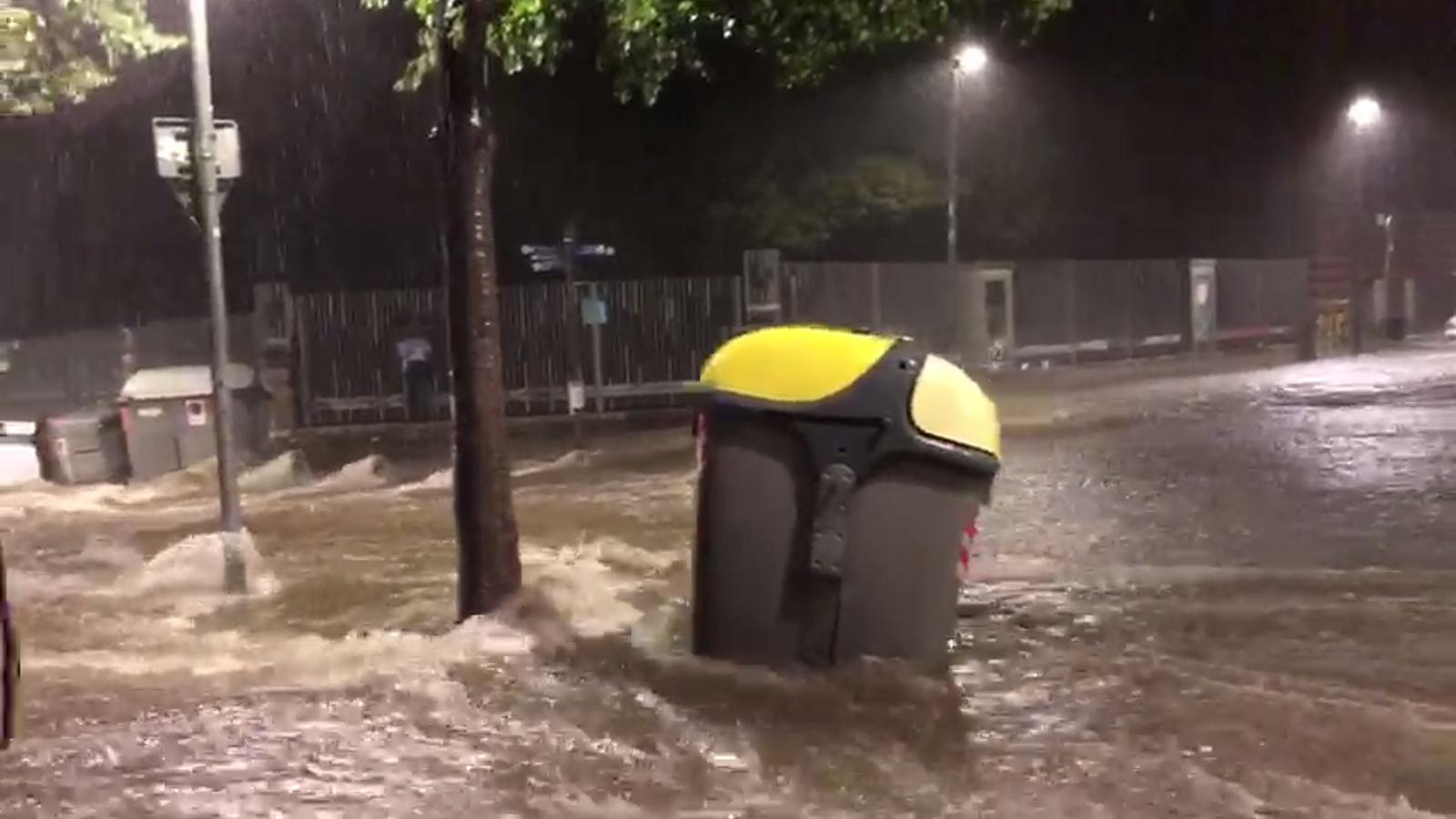 Un contenidor arrossegat per l'aigua de la pluja a l'entorn del Paral·lel