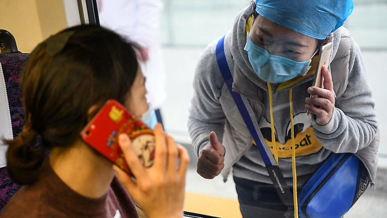Persones amb protecció contra el virus fent cua per comprar en una farmàcia.
