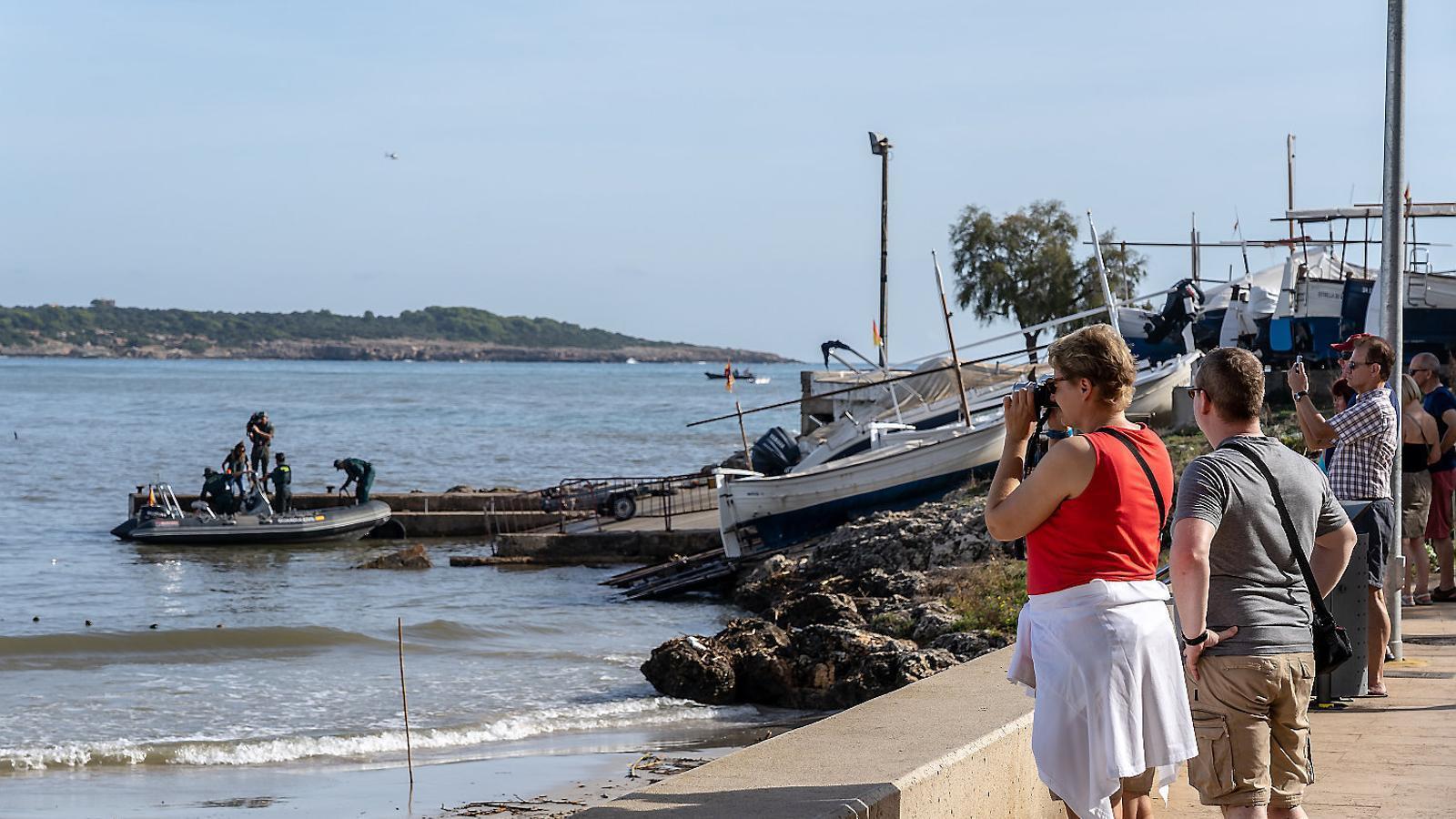 Dos turistes a la platja del municipi turístic de s'Illot observen una llanxa de la Guàrdia Civil que fa tasques de recerca dels desapareguts.