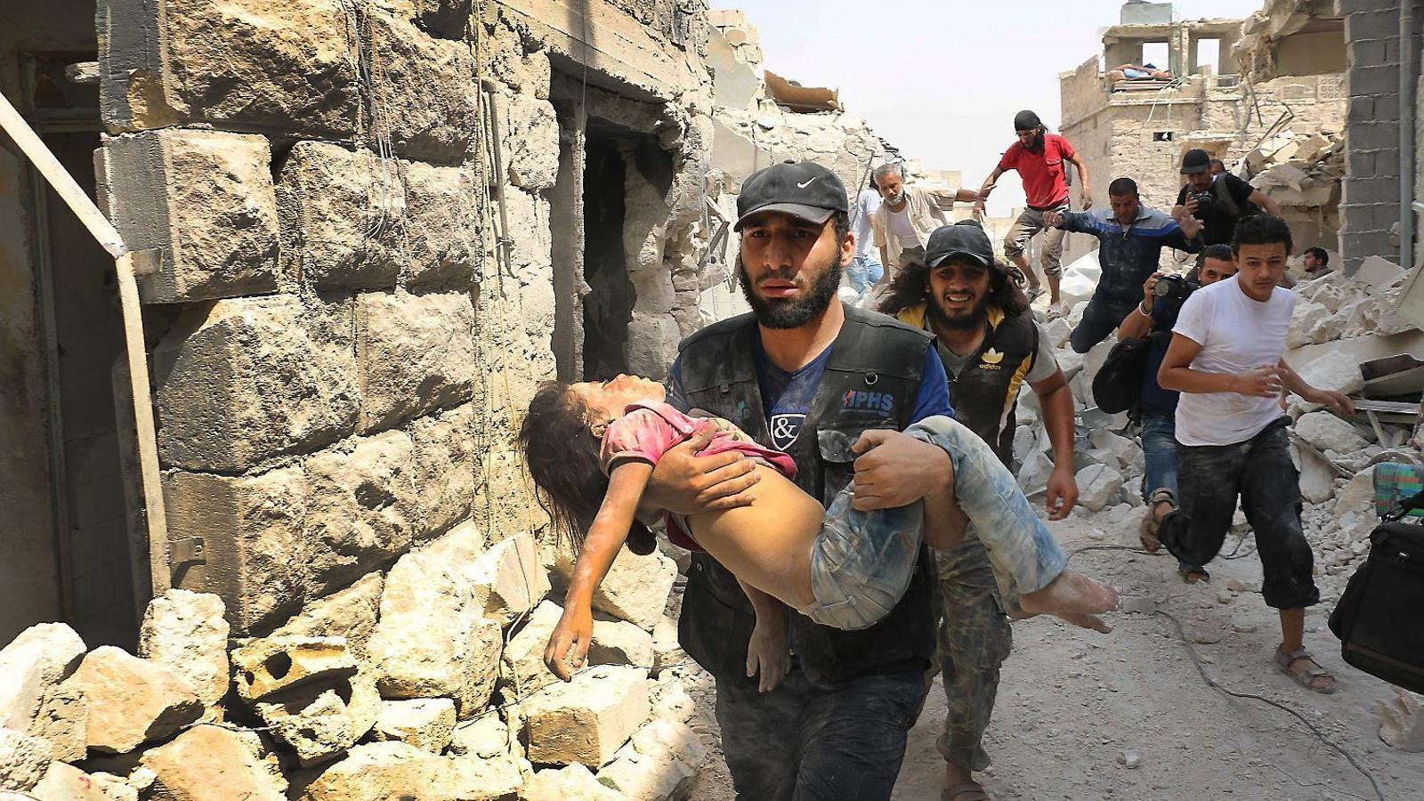 Un home portant una nena ferida per un atac amb barrils bomba, ahir al barri Bab al-Nairab, al sud de la ciutat siriana d'Alep.