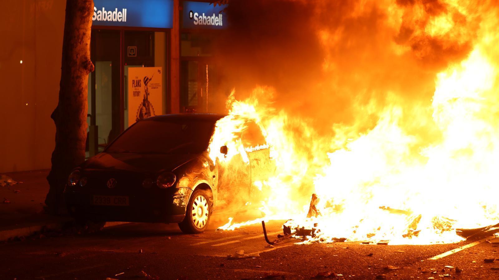 Cotxes cremant en la segona nit d'incidents a l'Eixample.
