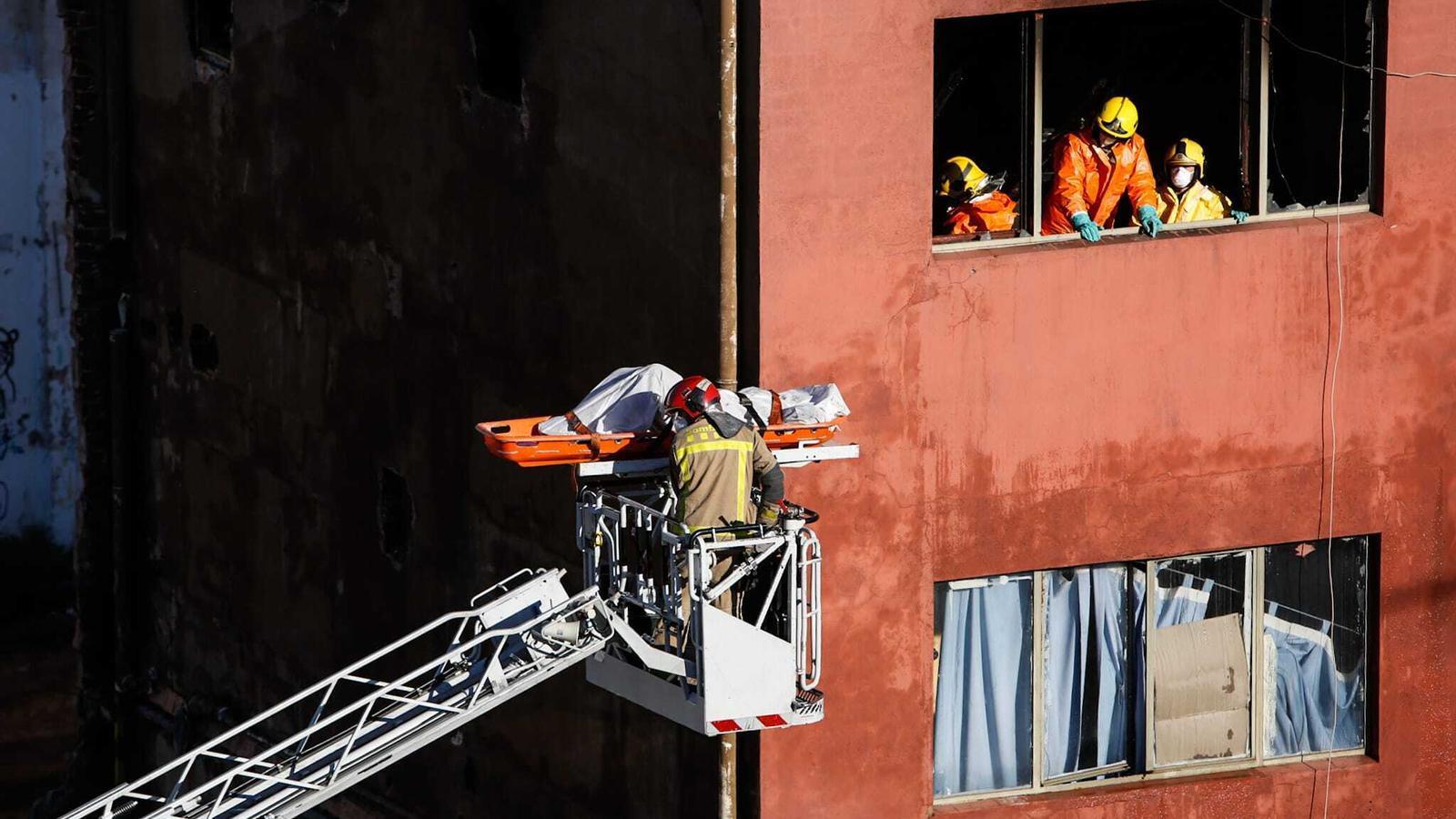 Un bomber traient el cos d'una de les víctimes