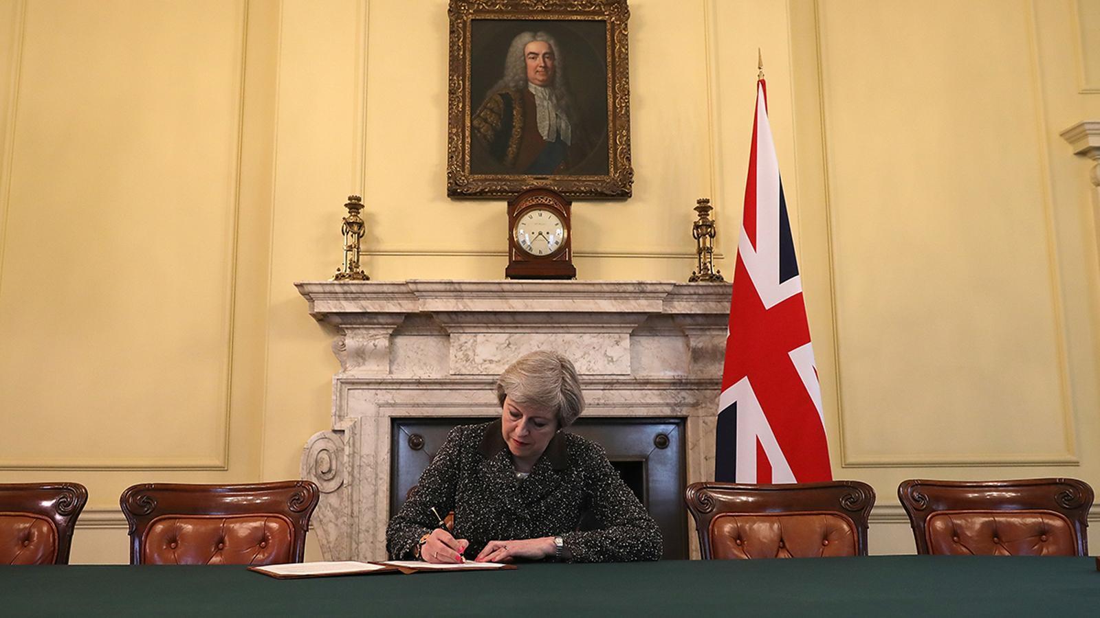 Theresa May signa la carta oficial del Brexit, en un despatx presidit per Robert Walpole, el primer primer minisitre britànic..
