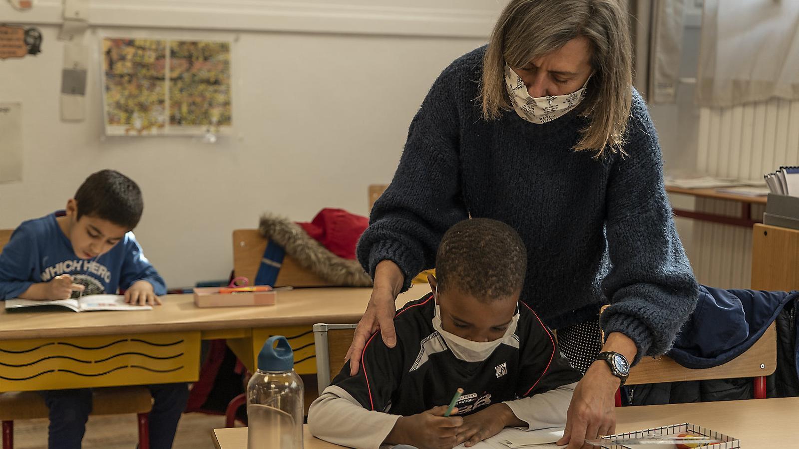 Una professora i un alumne, tots dos amb mascareta, durant una classe en una escola de París.