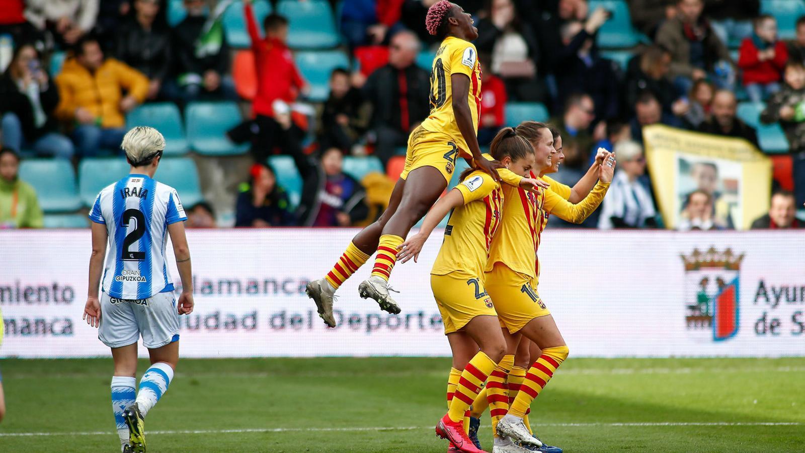 Asisat Oshoala saltant sobre les companyes en la celebració d'un gol mentre Iraia Iparraguirre es lamenta.