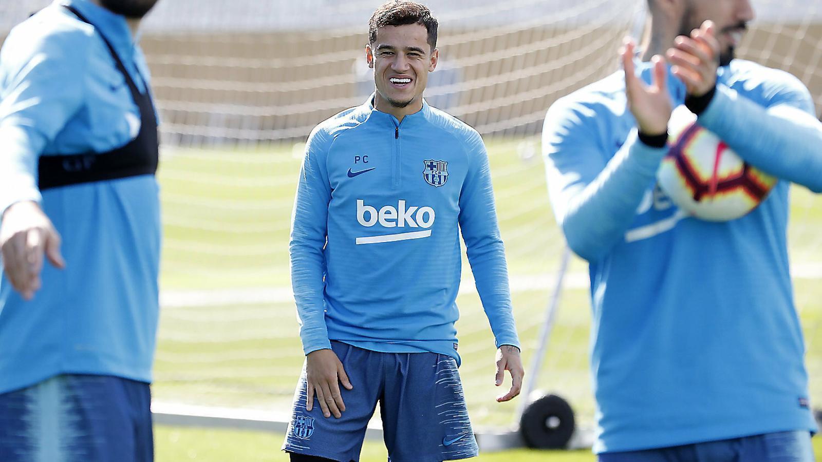 Coutinho somriu en un entrenament darrere del seu amic Suárez.