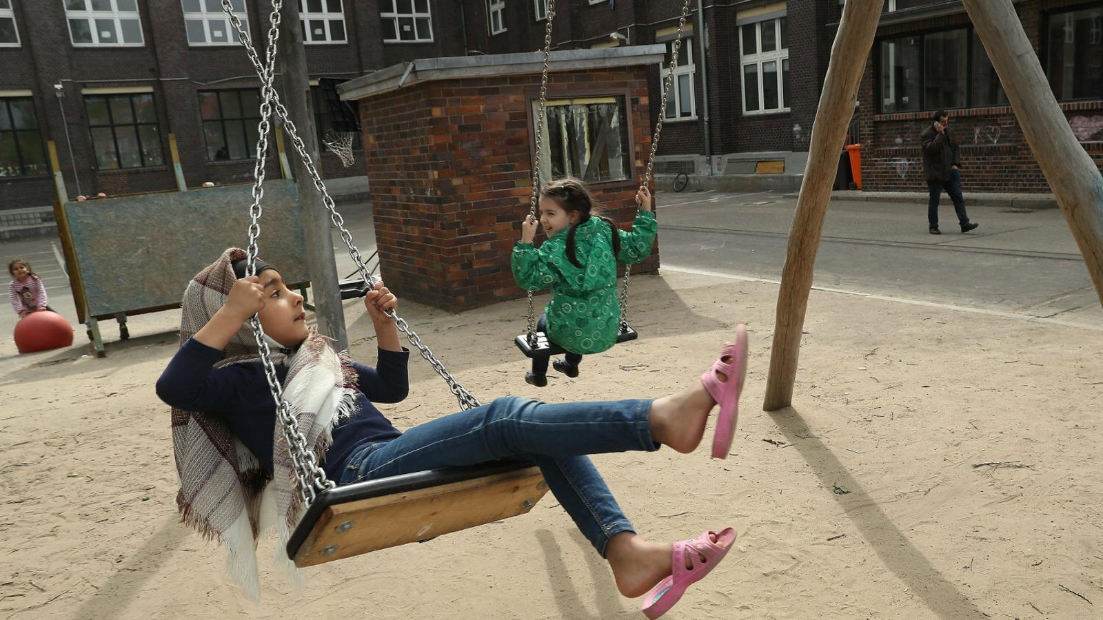 Dues nenes jugant a l'exterior d'un edifici de Berlín d'acollida d'immigrants i refugiats. Europa necessita més immigració per assegurar-se el relleu generacional.