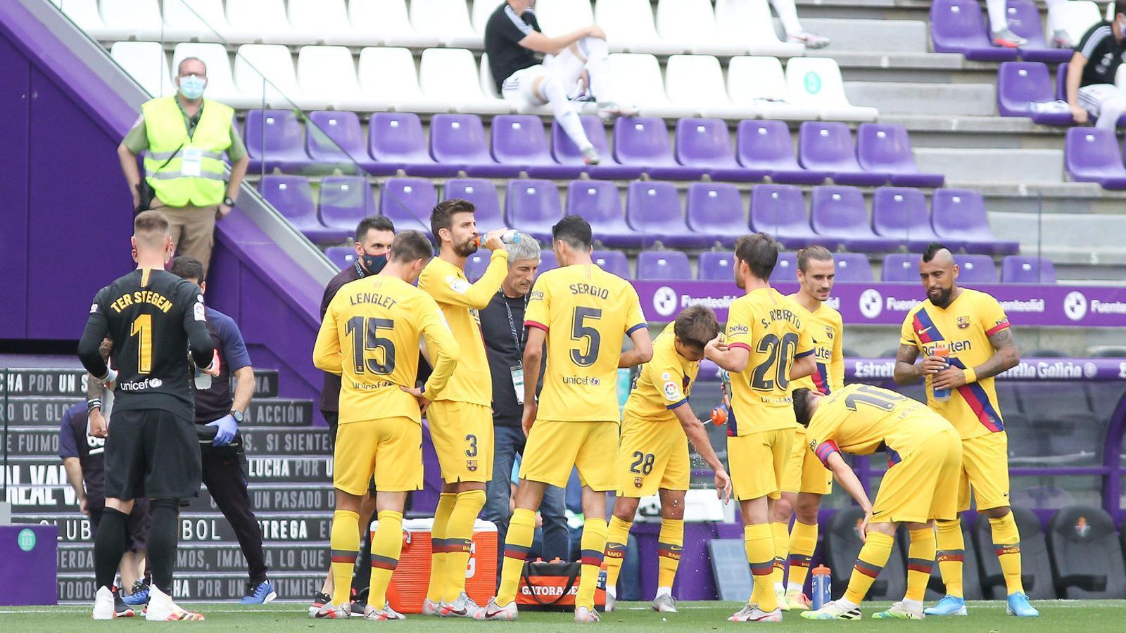 Els jugadors del Barça refrescant-se durant la primera part del partit de dissabte a Valladolid.