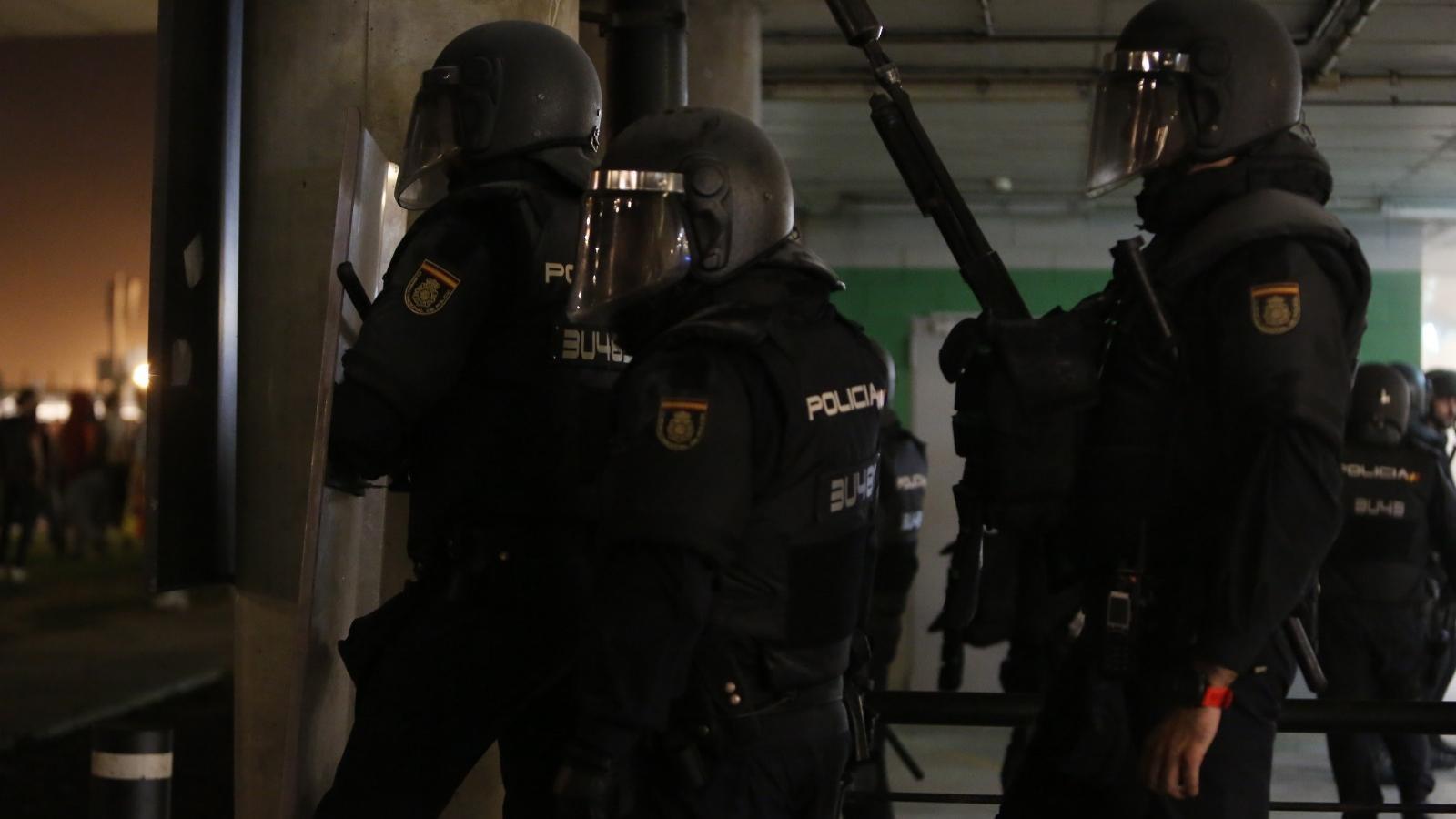 Tres policies nacionals, un dels quals escopeter, preparats per actuar al pàrquing de l'aeroport del Prat