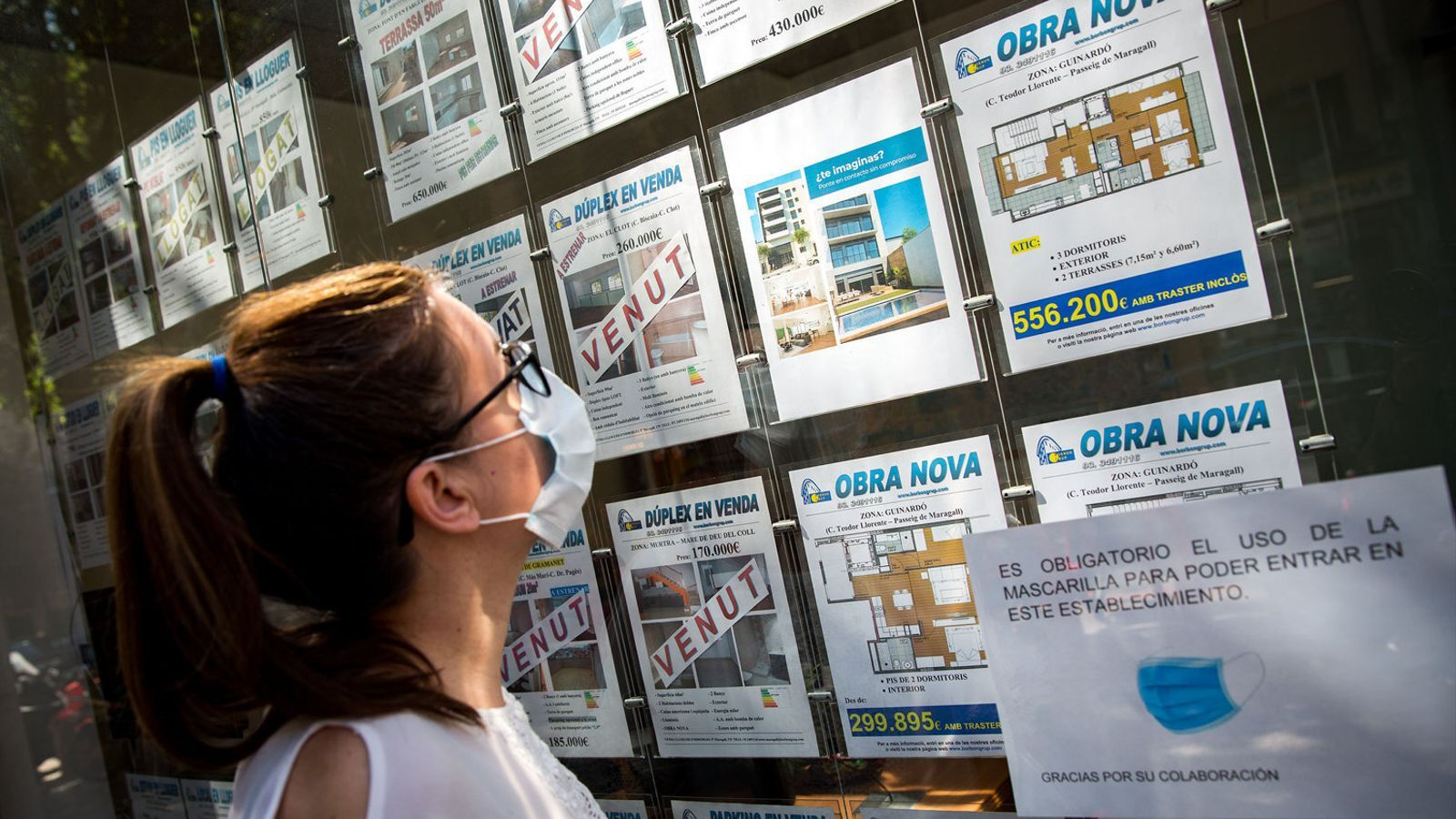 Una dona amb mascareta mirant les ofertes d'una immobiliària a Barcelona.