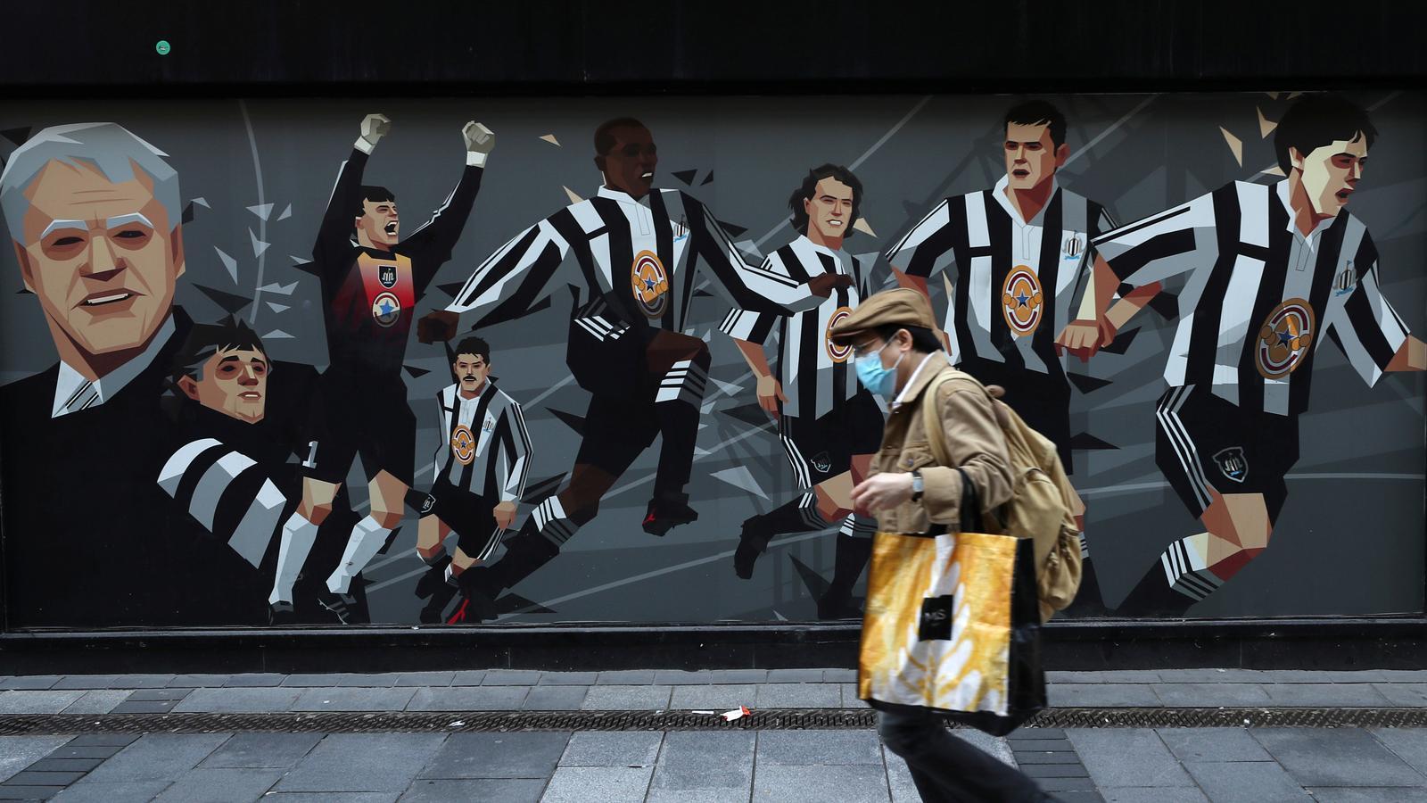 Un home cobert amb una mascareta passa al davant d'un grafit que representa els jugadors del Newcastle FC