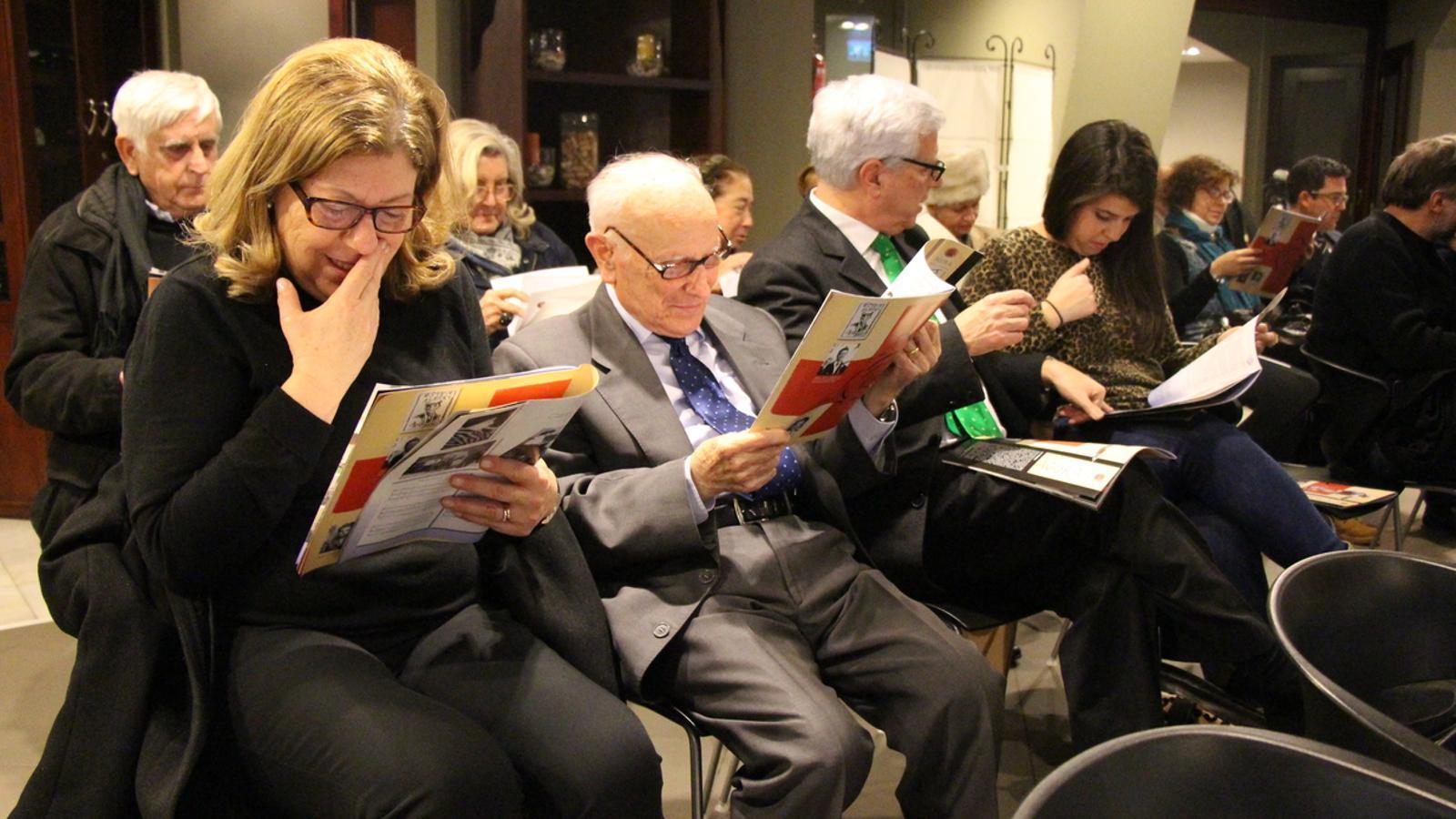 Francesc Badia, un dels premiats l'any 2013, fulleja la revista junt a alguns familiars