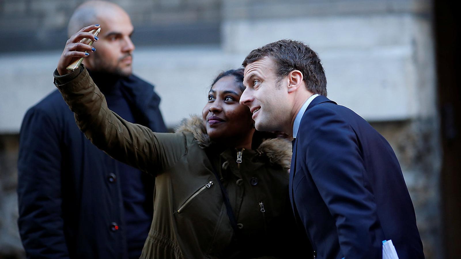 Macron fent-se una fotografia amb una simpatitzant en un carrer de París.