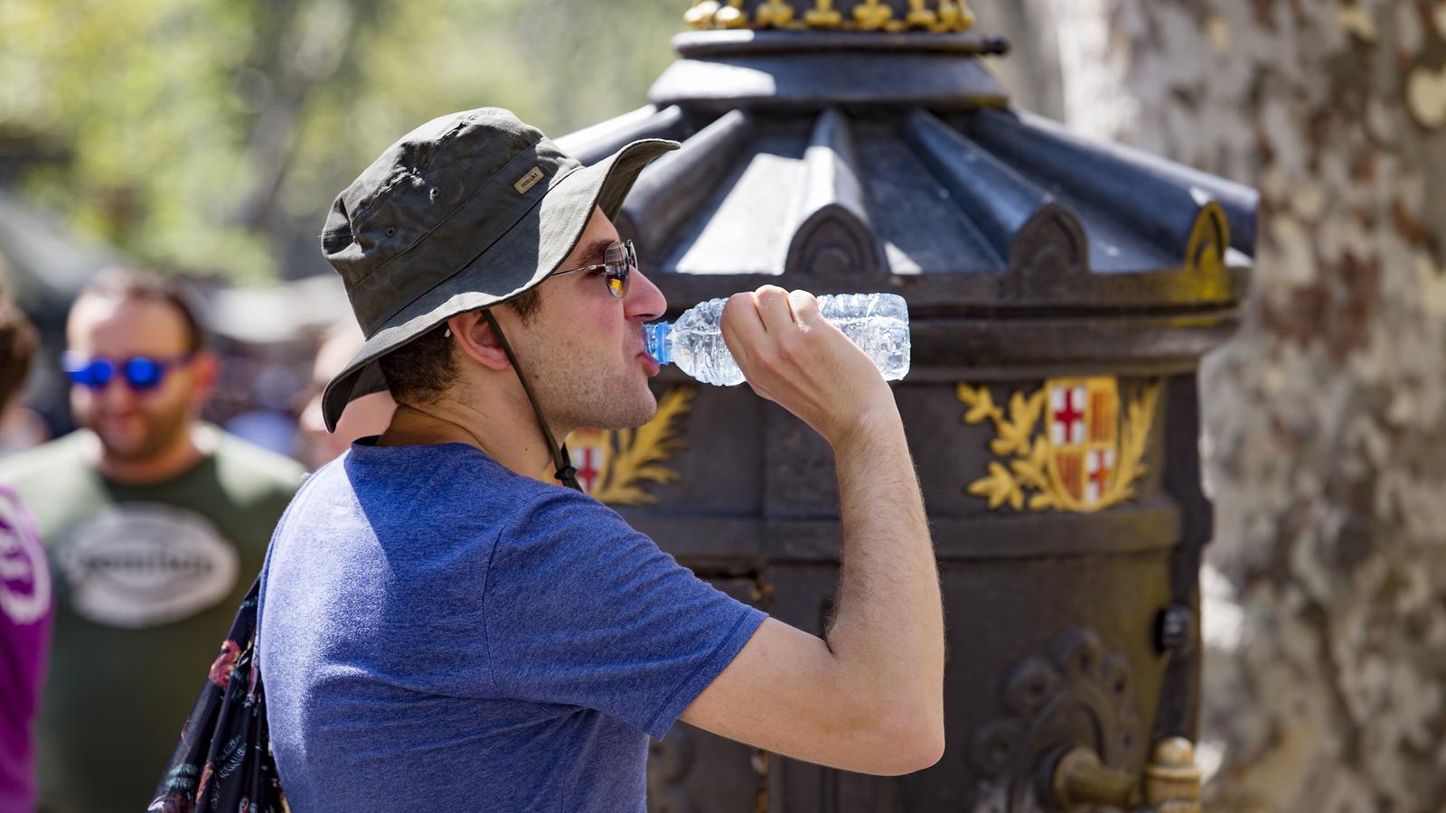 Un home bevent aigua a Barcelona durant l'onada de calor