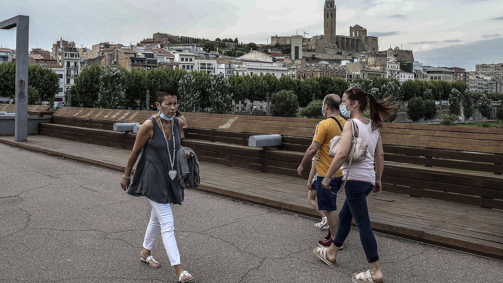 Veïns de Lleida caminant pel carrer, amb la Seu Vella al fons.