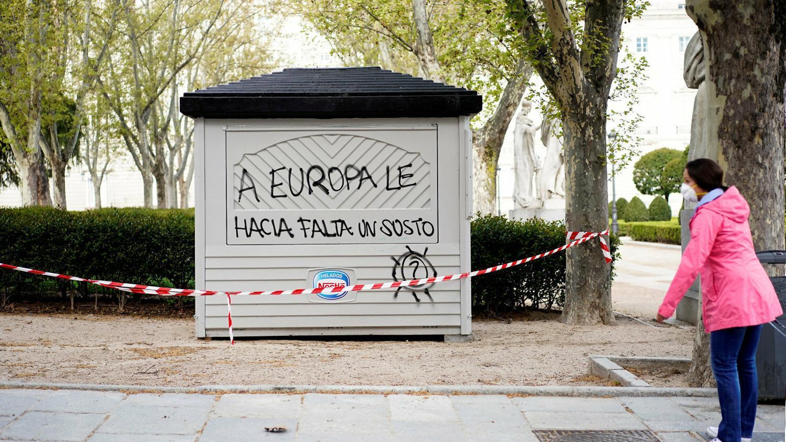 Una dona amb una màscara protectora davant un quiosc tancat en una plaça de Madrid. Els ministres de Finances de l'eurozona es reuneixen avui per intentar aprovar el primer escut econòmic davant la crisi del coronavirus.