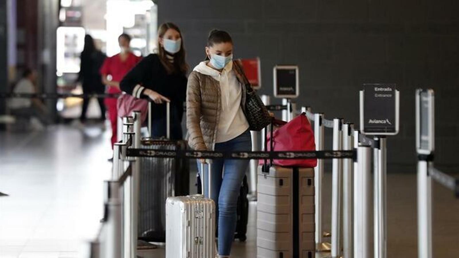 Unes turistes protegides amb mascareta i carregades amb maletes.