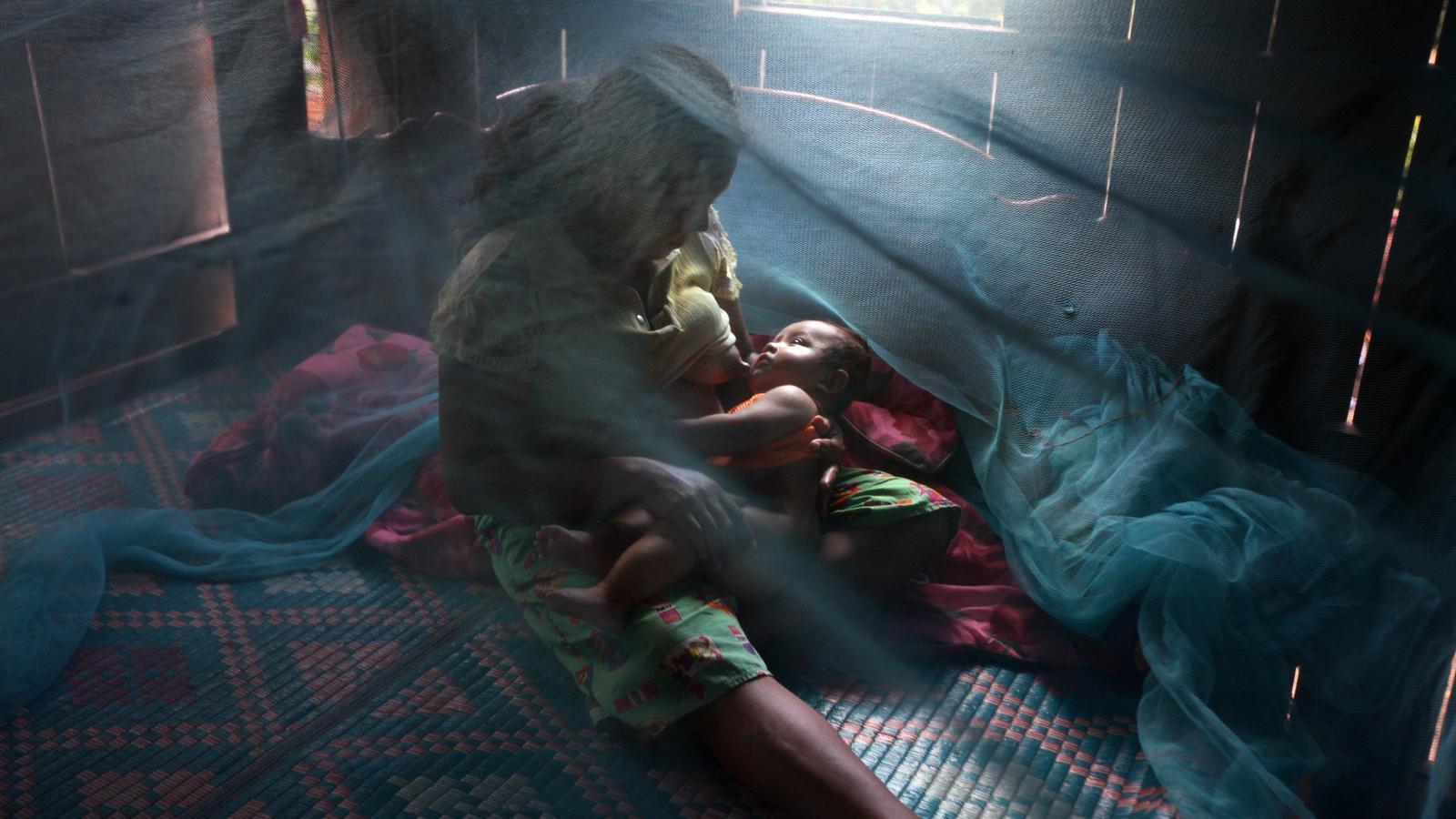 Una mare alletant el seu nadó, protegits per una mosquitera contra la malària, en un poblat de la província cambodjana de Pailin