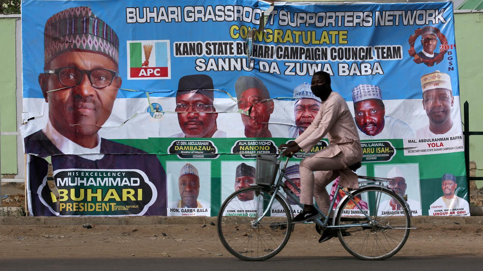 Un home passa per davant d'un cartell que demana el vot per la reelecció del president Buhari