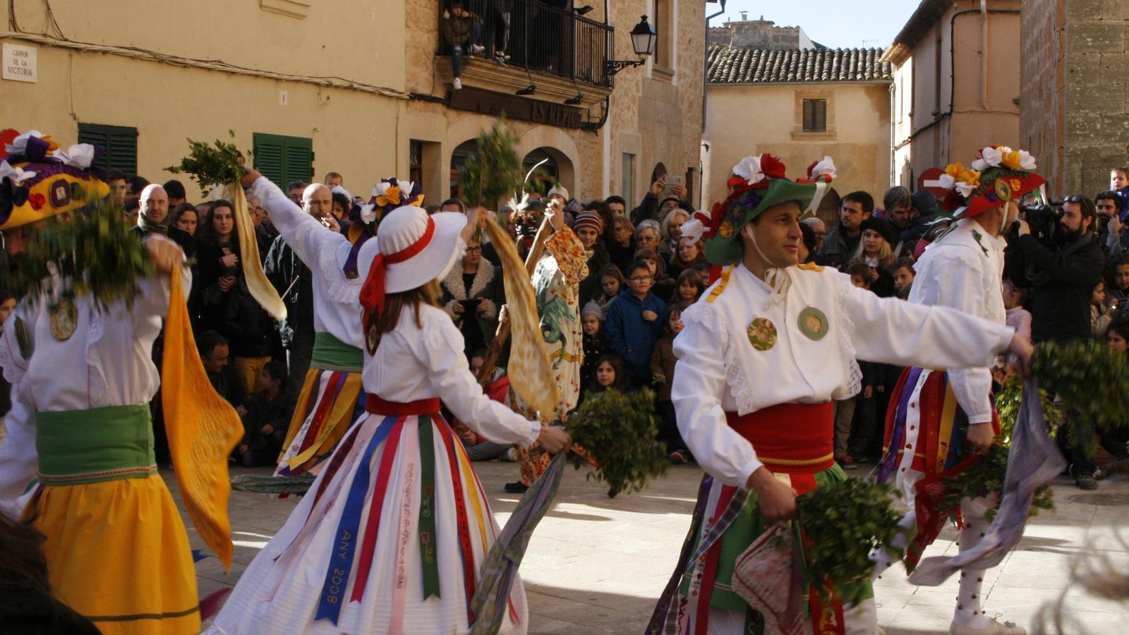 Una multitud de gent segueix les danses a la placeta, i també des d'alguns balcons.