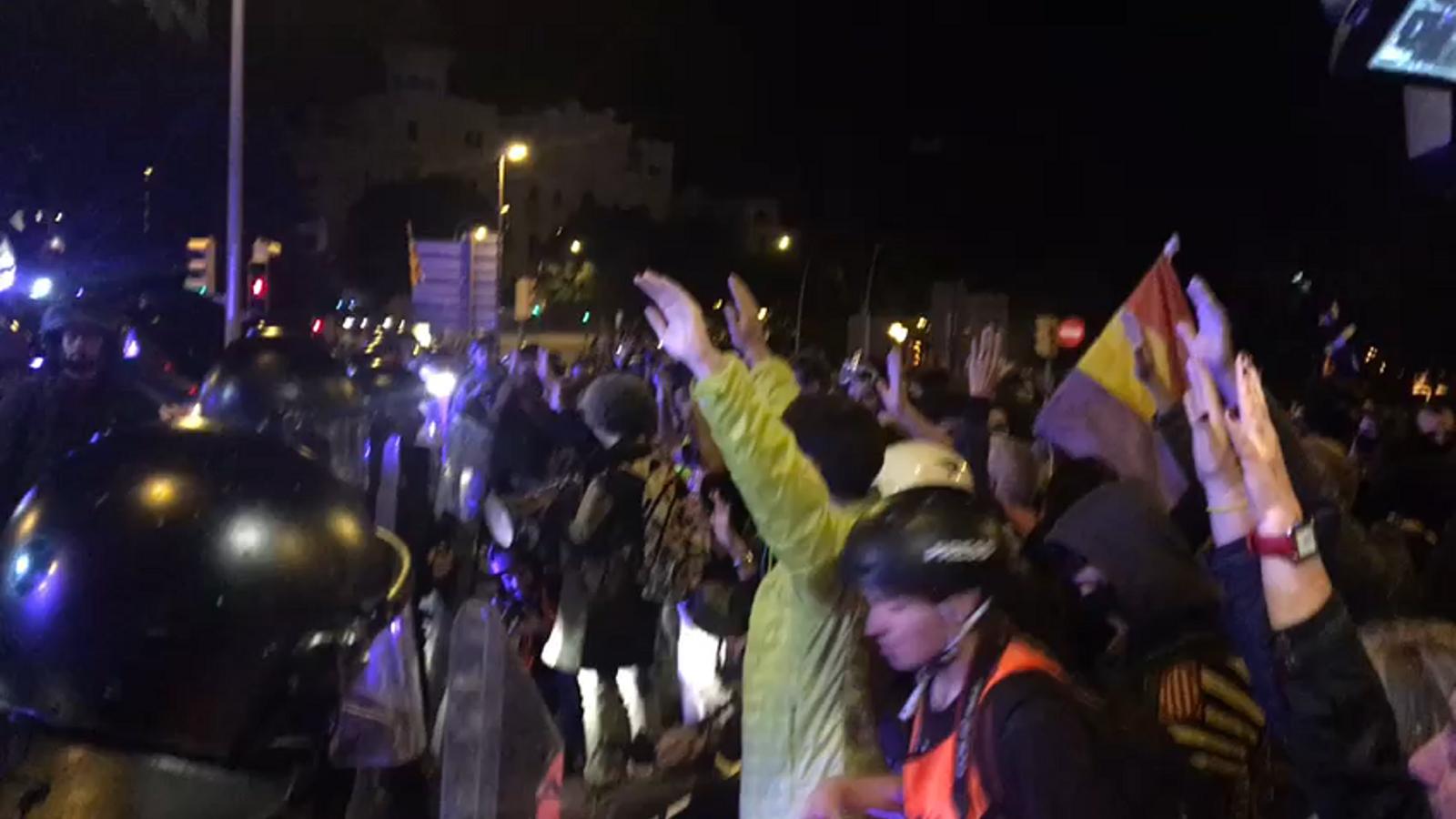 Un grup de manifestants es posen davant del cordó policial amb les mans alçades