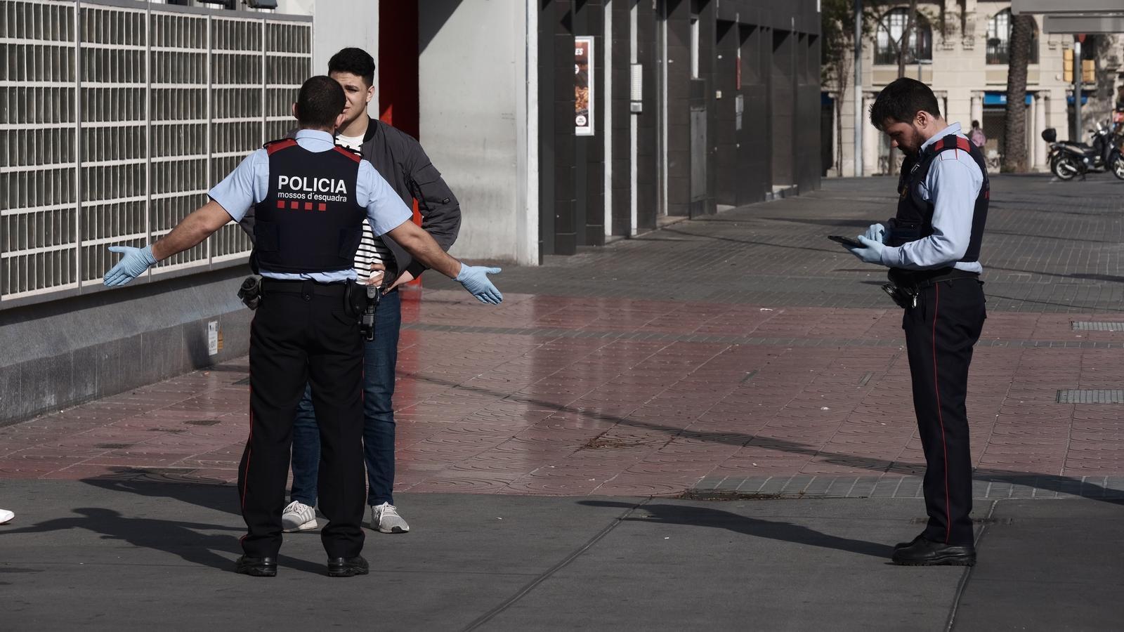 Dos agents dels Mossos comprovant aquest dilluns si un ciutadà que anava per la plaça Espanya de Barcelona compleix el confinament