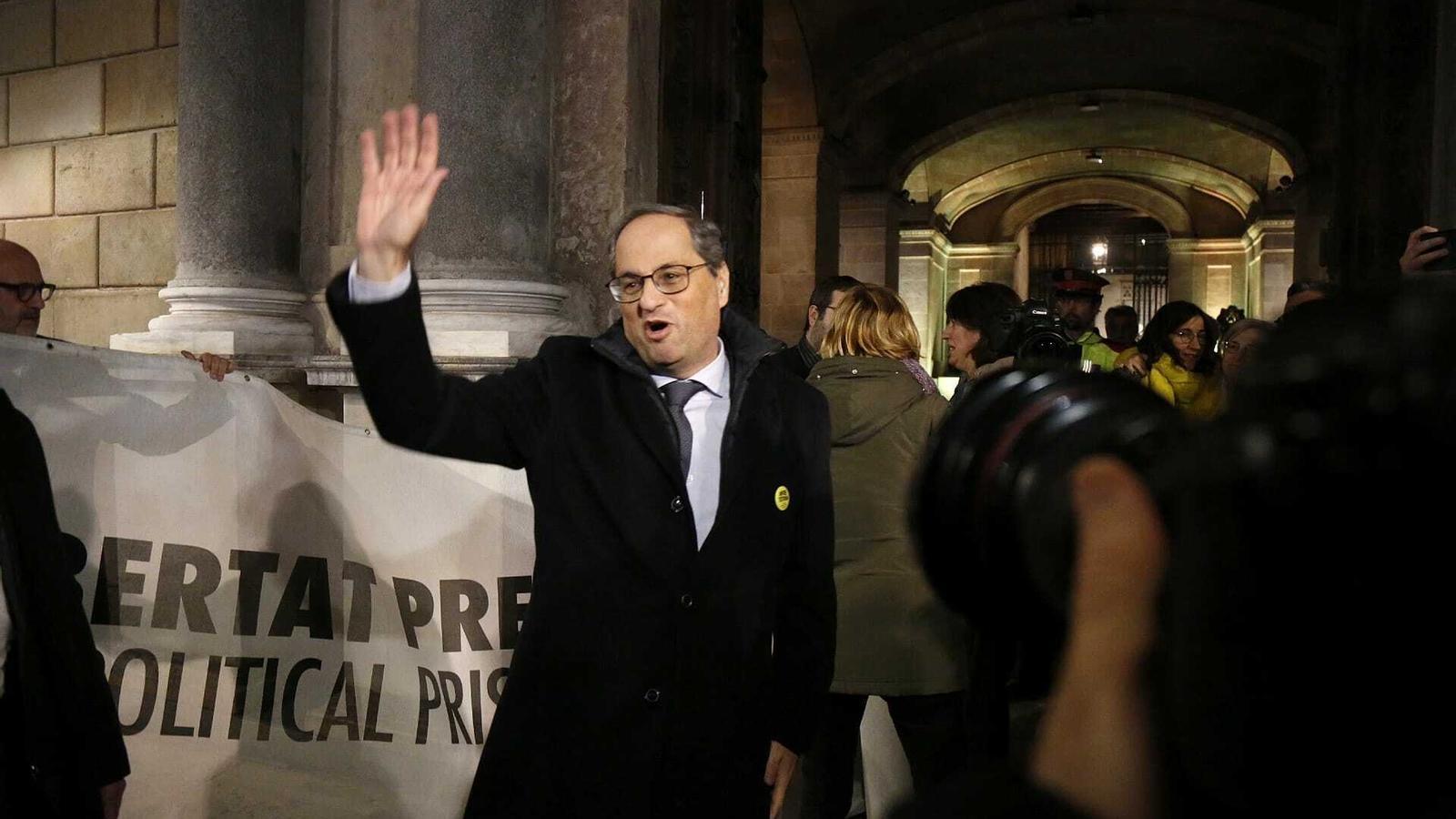 El president Torra, saludant els concentrats a la porta de Palau. Al seu darrere, la pancarta dels presos