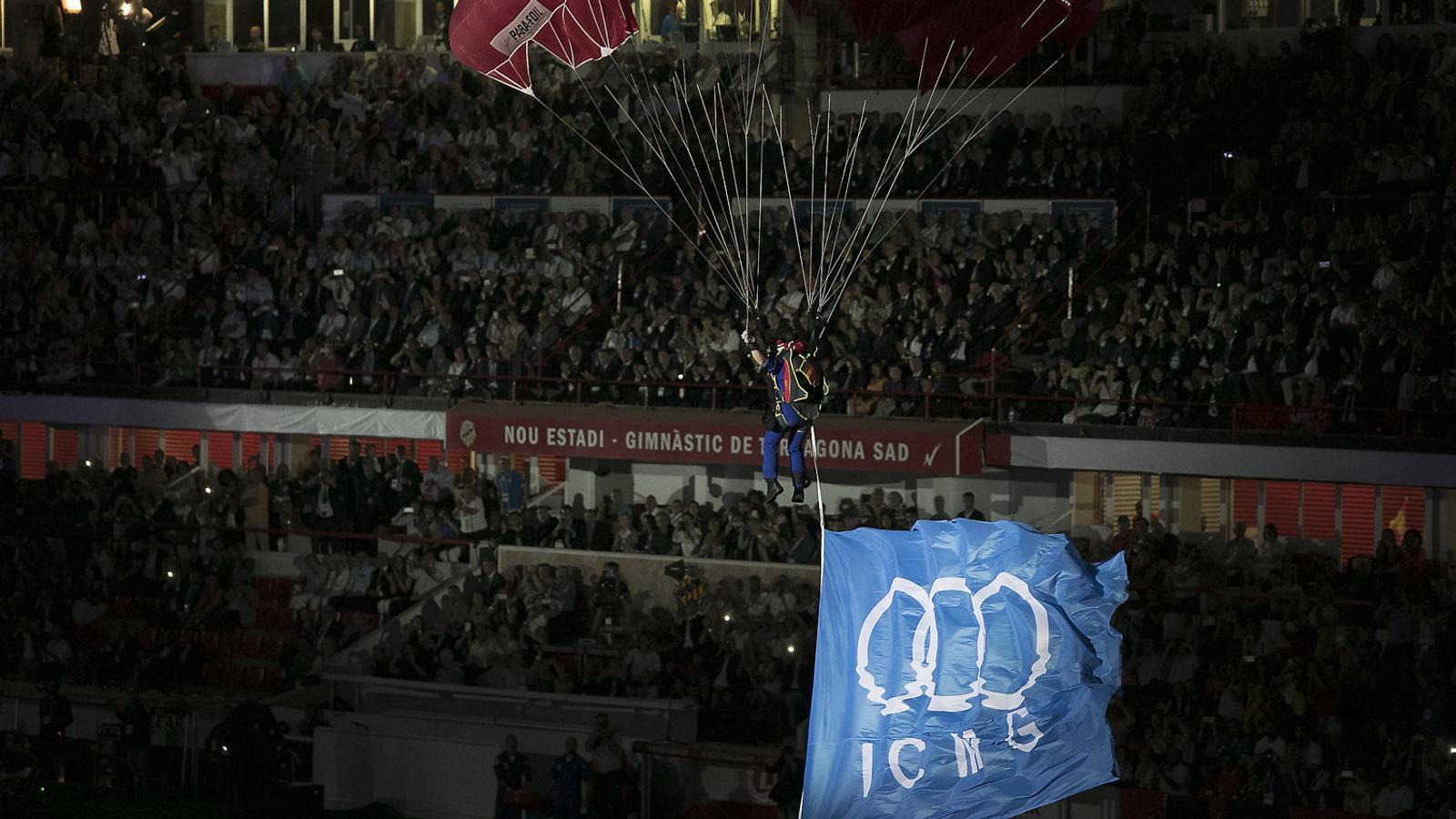 La bandera dels Jocs Mediterranis aterrant amb paracaigudista al Nou Estadi de Tarragona.