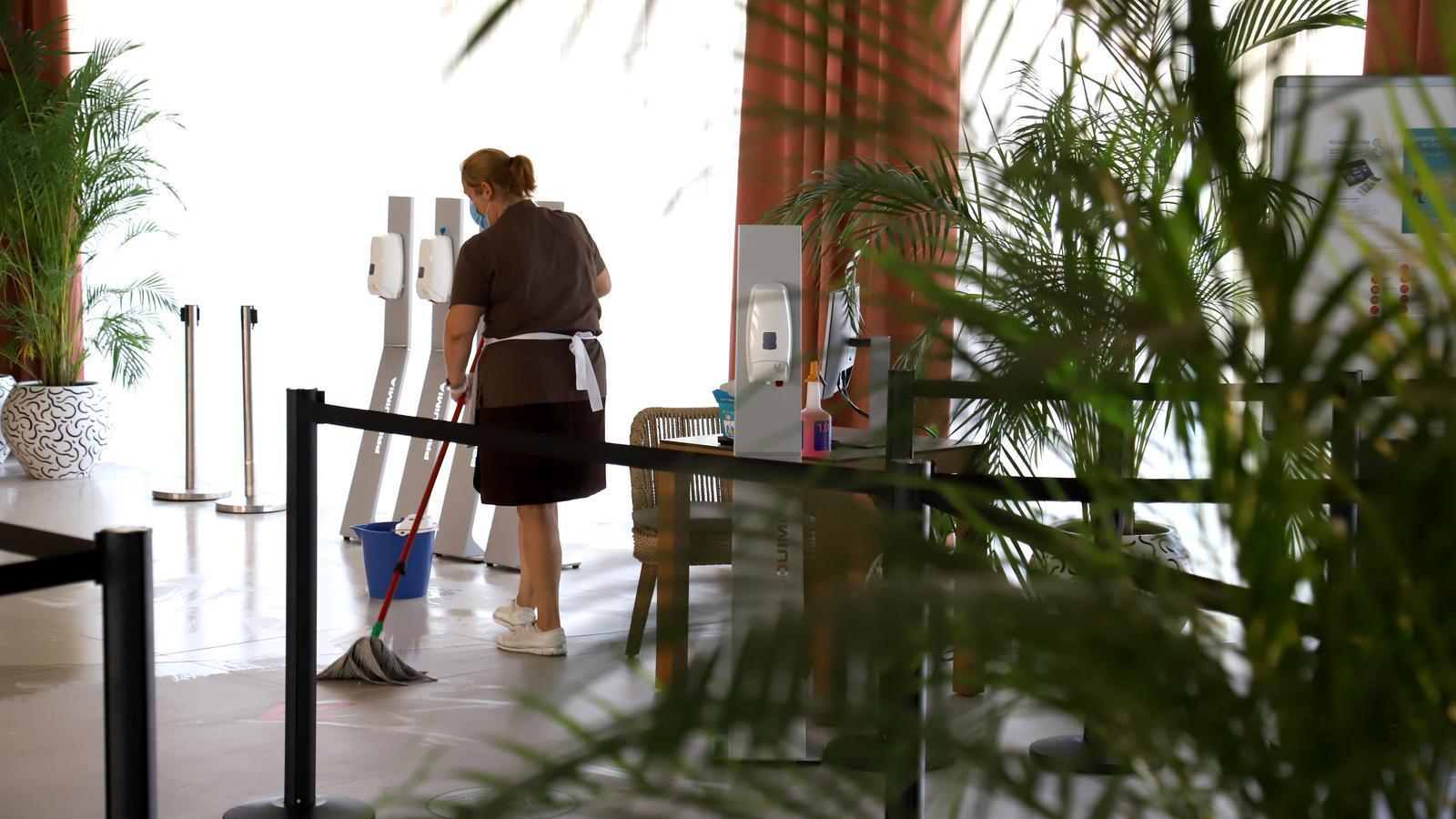 Una dona neteja l'entrada d'un hotel aquest estiu.