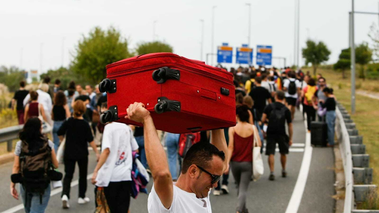 Turistes intentant agafar taxis que es barregen amb manifestants que van cap a la T1