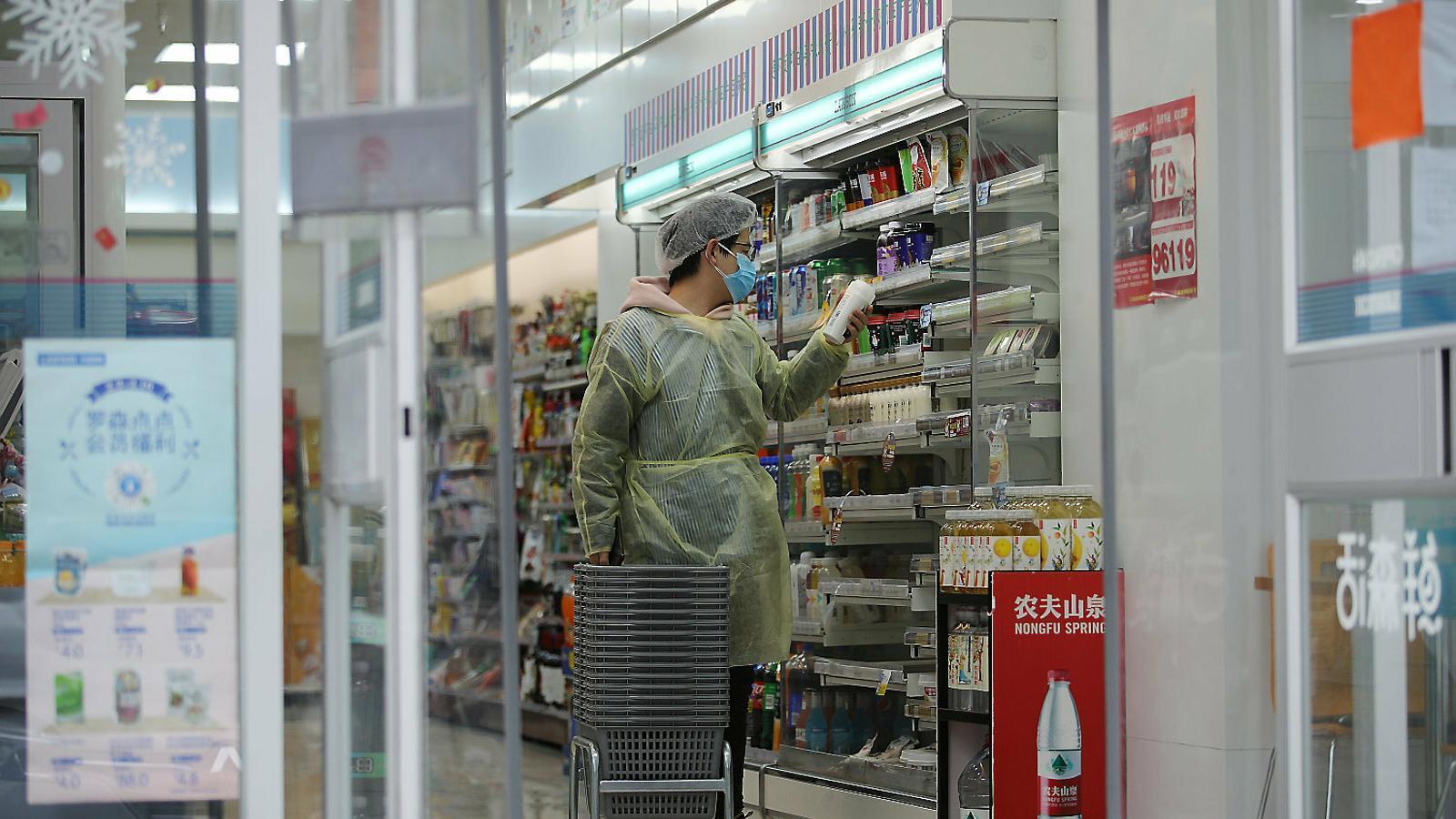 01. Una clienta en un supermercat a la ciutat de Wuhan, epicentre de l'epidèmia.  02. Un venedor de carn a Xangai.  03. Una perruquera arreglant els cabells d'una clienta a Xangai.  04. Treballadors d'un restaurant jugant a cartes a Pequín.