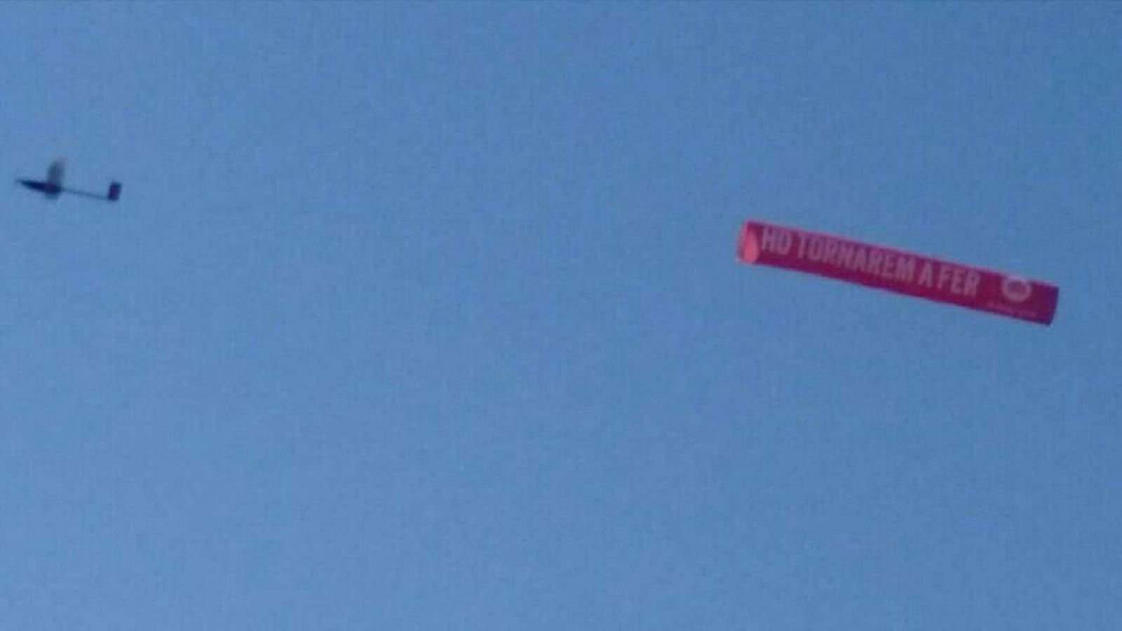 Una pancarta d'Òmnium amb el lema 'Ho tornarem a fer' sobrevola aquest estiu les platges catalanes