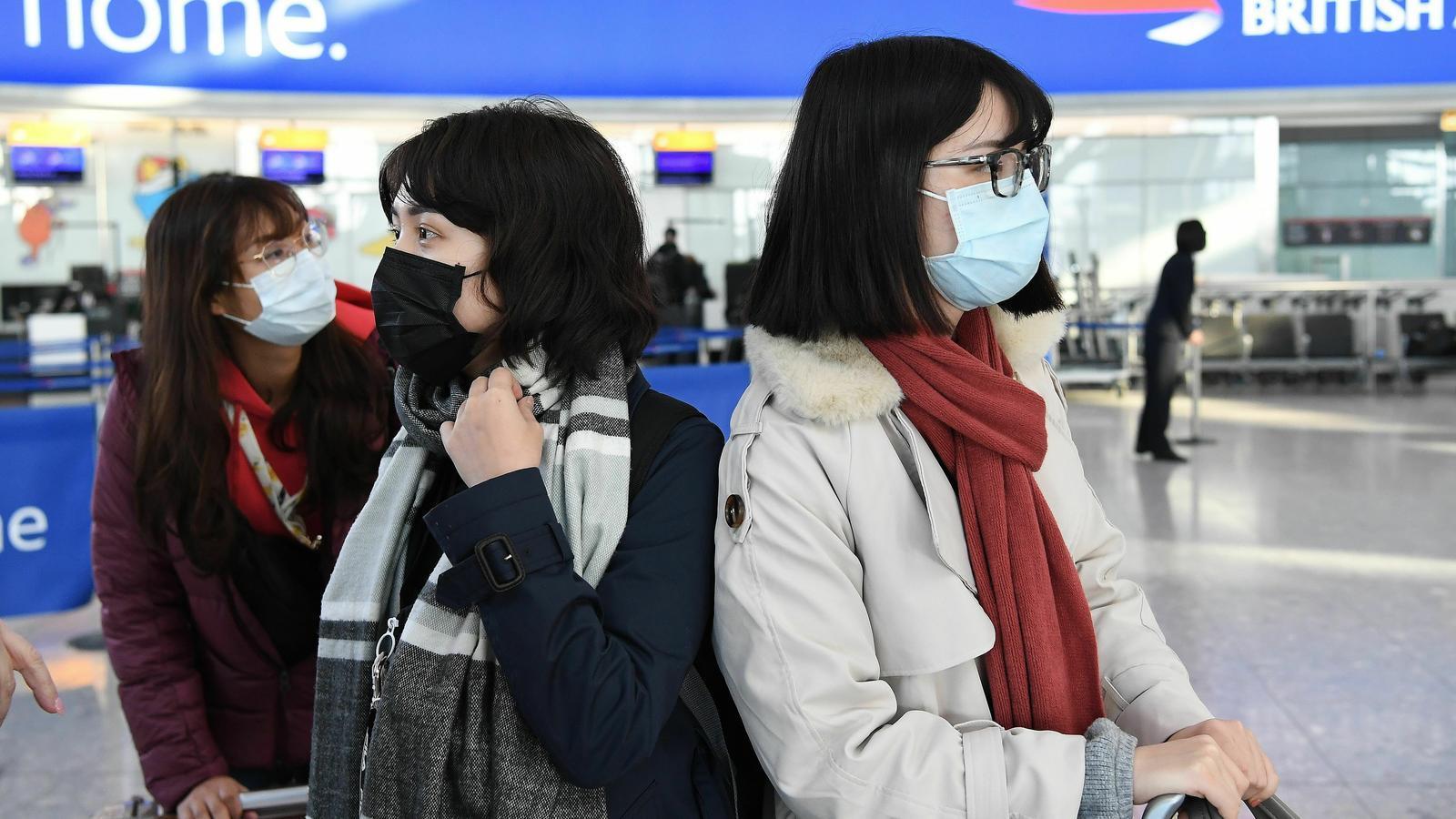 Tres passatgeres amb mascaretes esperen a l'aeroport Heathrow, a Londres.