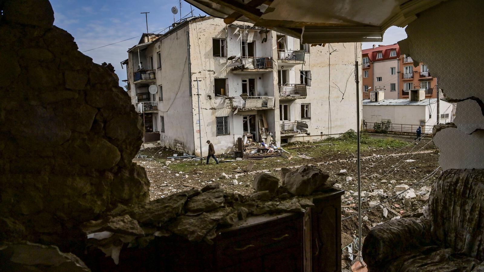 Un home camina davant d'una casa destruïda a Stepanakert, la principal ciutat de la regió de Nagorno-Karabakh