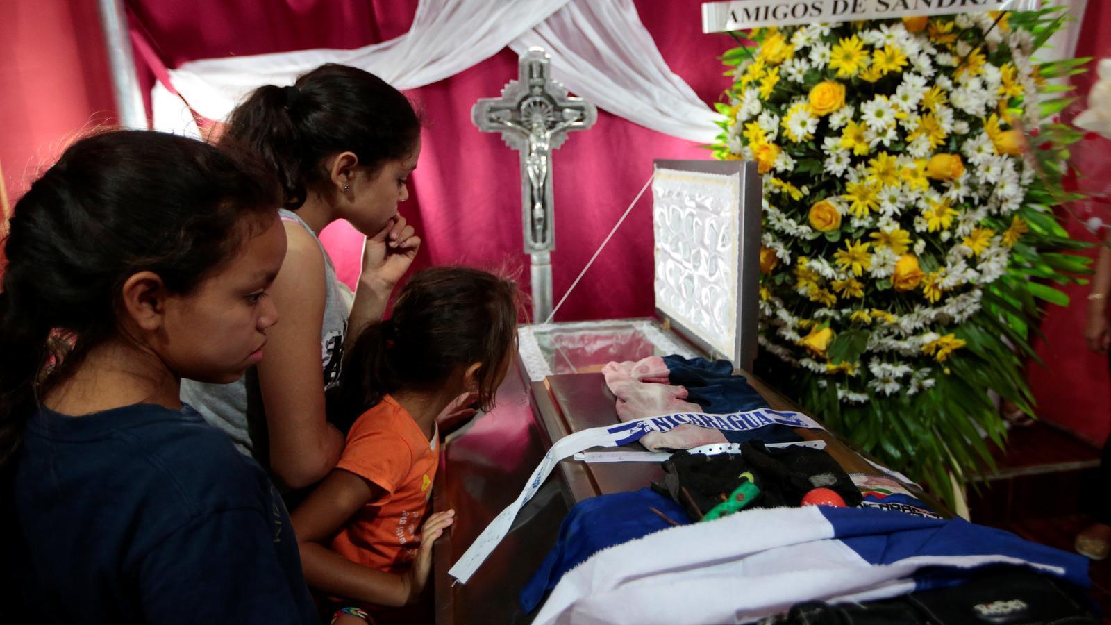 Uns nens miren la tomba d'un dels estudiants que va morir durant els atacs amb la policia a la Universitat Nacional Autònoma de Nicaragua.