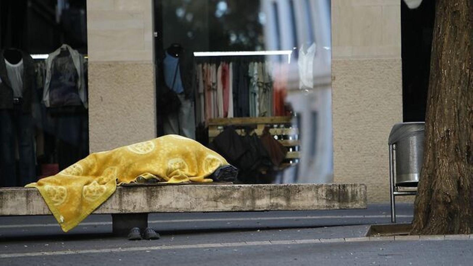 Una persona sense sostre dorm en un banc d'un carrer de Palma.