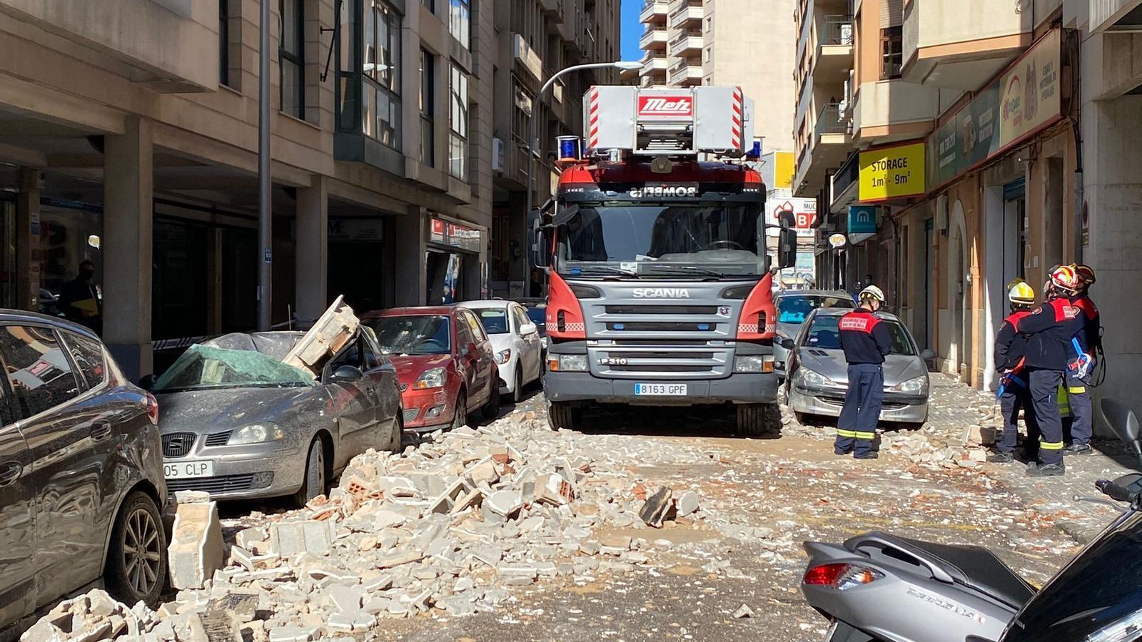 Els Bombers han hagut d'actuar per poder treure del carrer les restes de la cornisa.