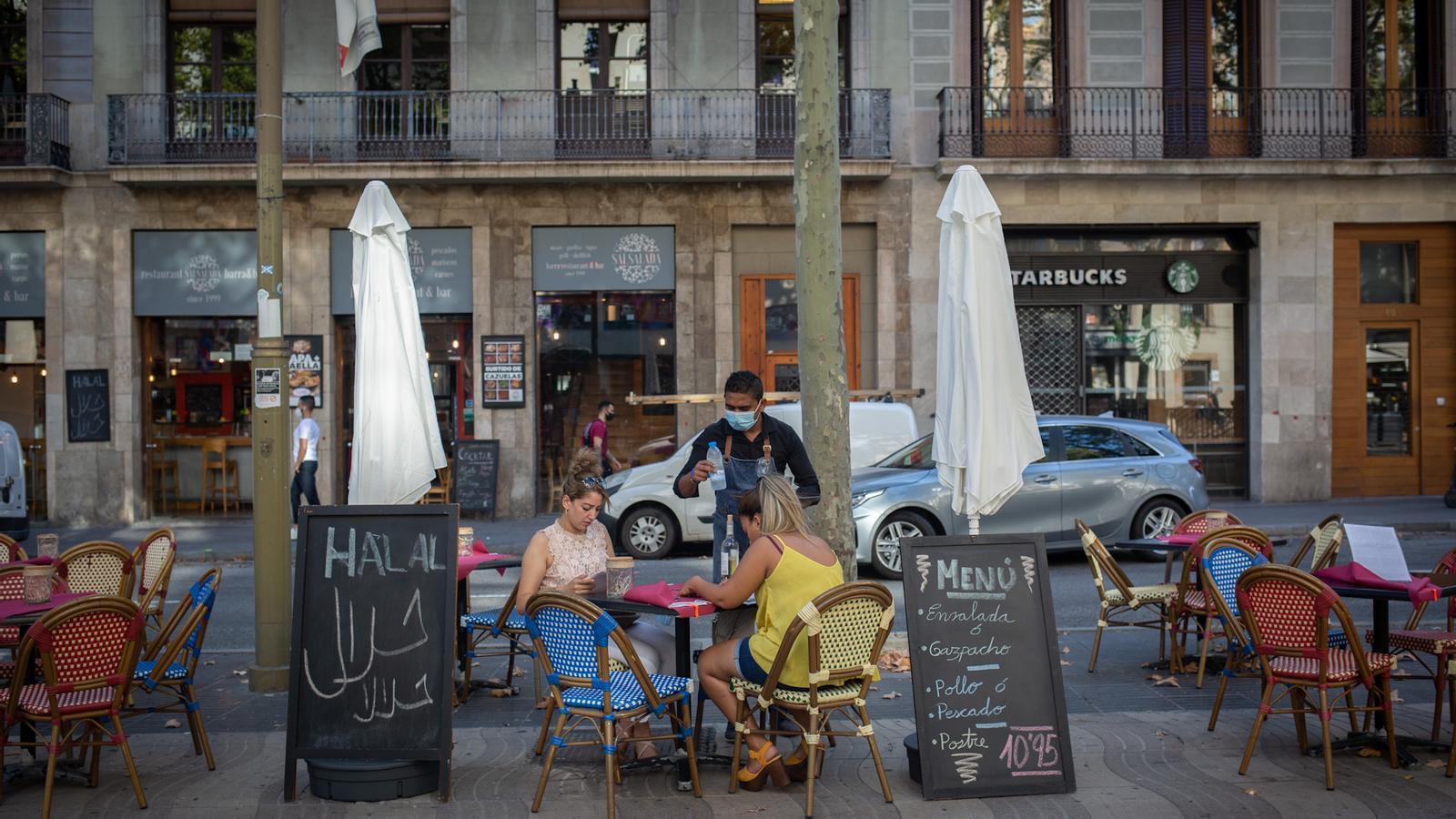 Dues dones a la terrassa d'un bar de Barcelona