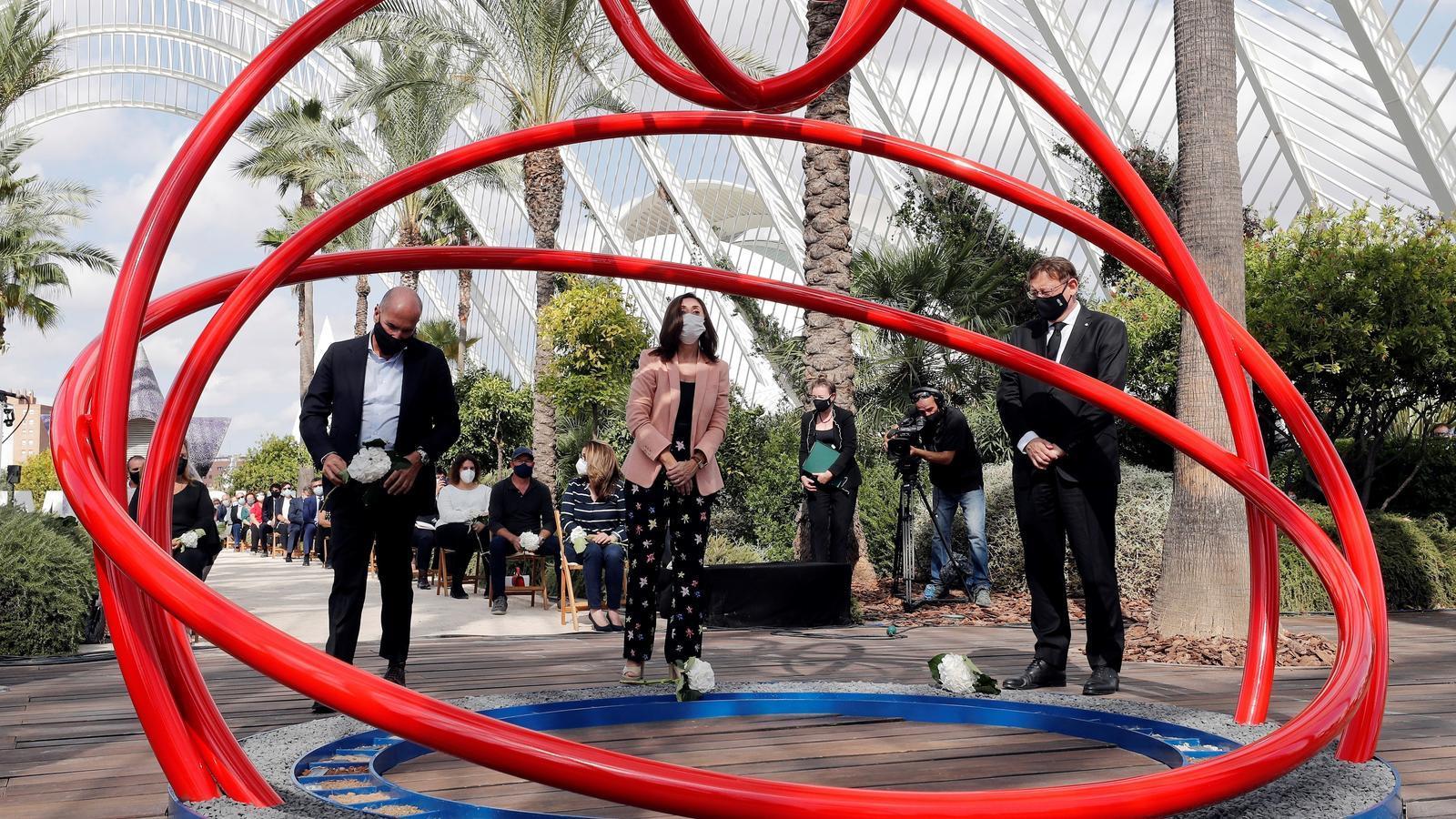 El cap del Consell, Ximo Puig, junt al periodista Lluís Motes i la cap de la Unitat de Malalties Infeccioses de l'Hospital General d'Alacant, Esperanza Merino, durant la inauguració de l'escultura 'En rècord' de l'artista alcoiana Rosana Antolí