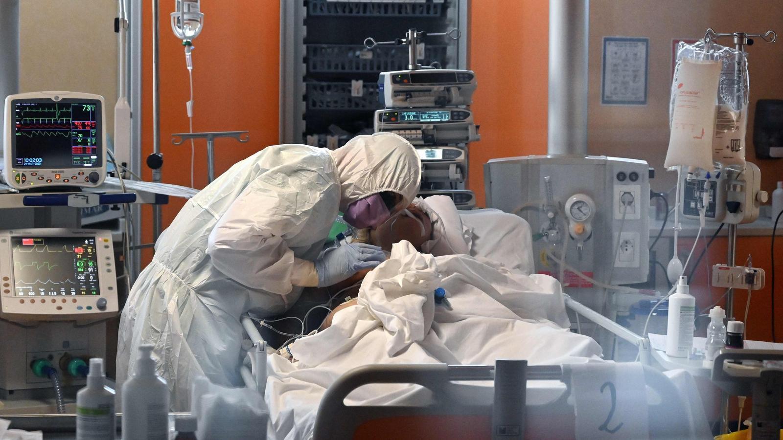 Un sanitari amb l'equip de protecció atén un pacient en un hospital de Roma