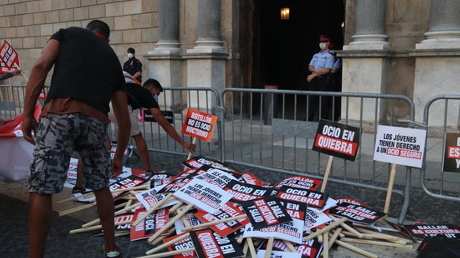 Dos treballadors de l'oci nocturn deixant les seves pancartes de protesta davant el Palau de la Generalitat el 29 de juliol de 2020.