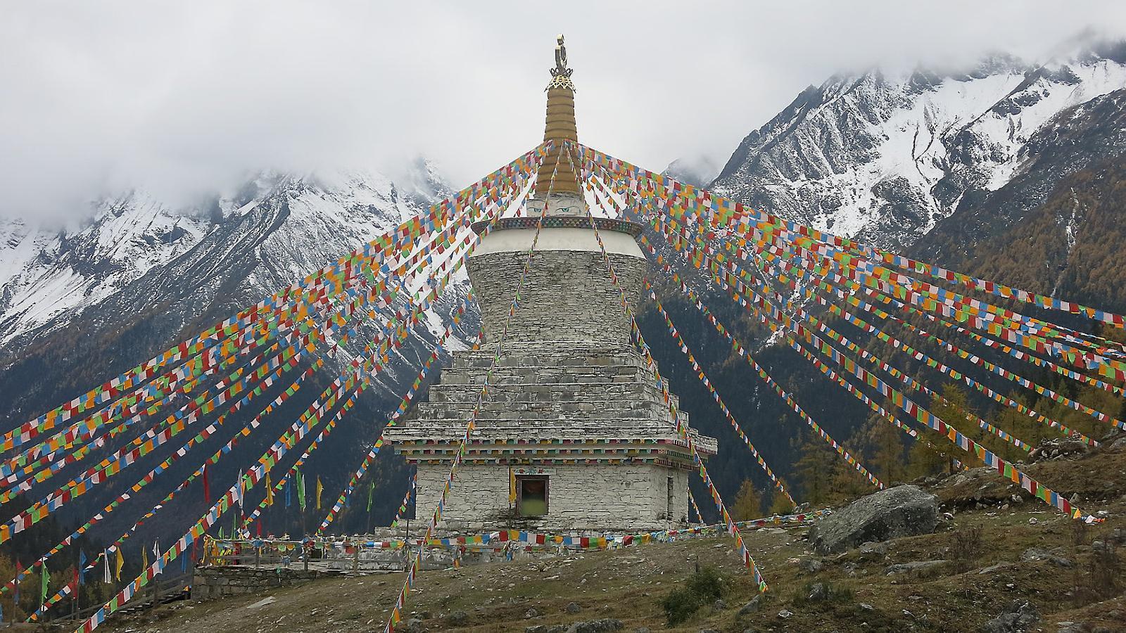 A dalt, una stupa amb banderes d'oració tibetanes, a les muntanyes Siguniang. A baix, monjos debatent a la porta del temple principal del monestir de Labrang.