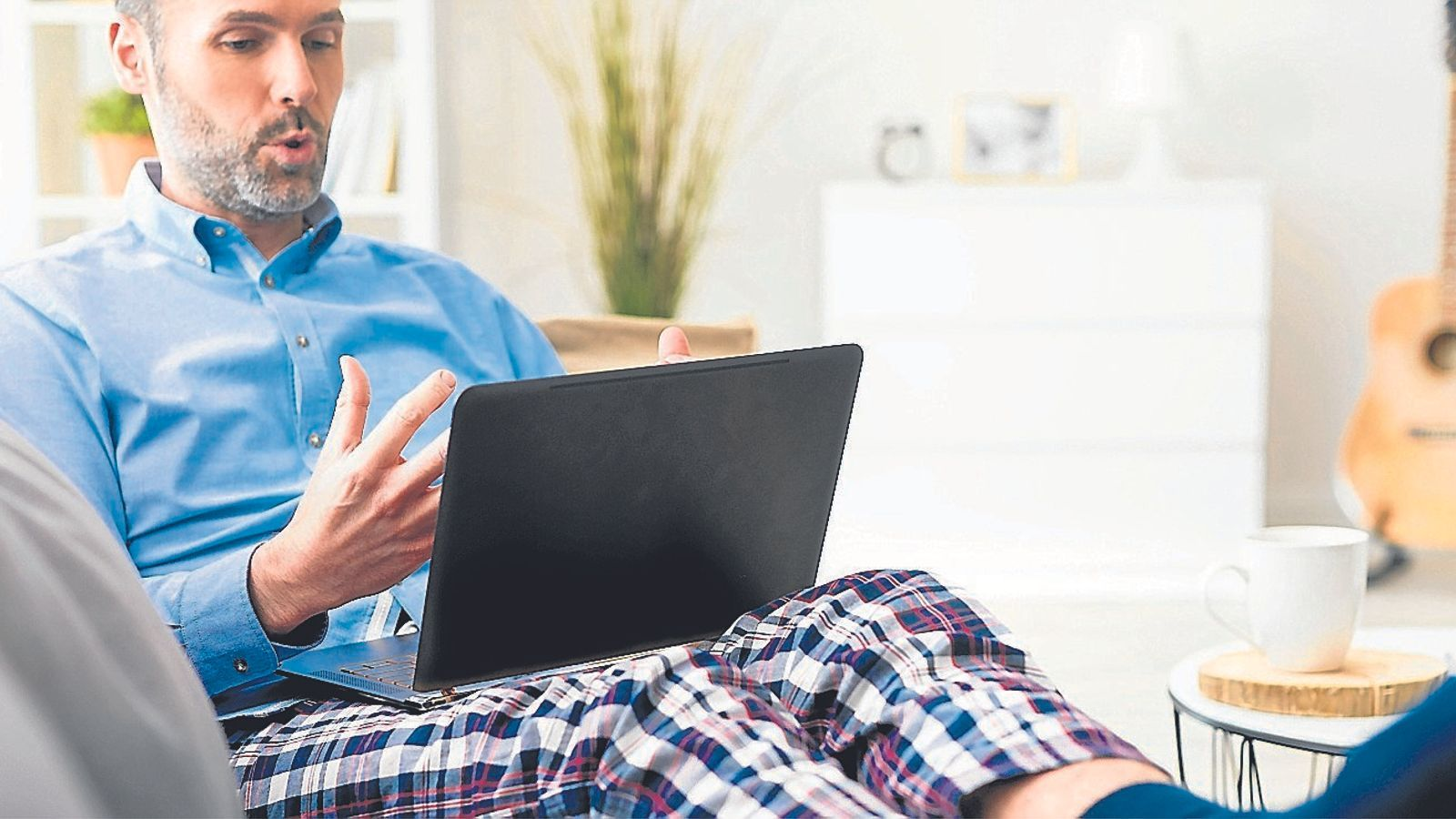Un home teletreballa des de casa amb els pantalons de pijama.