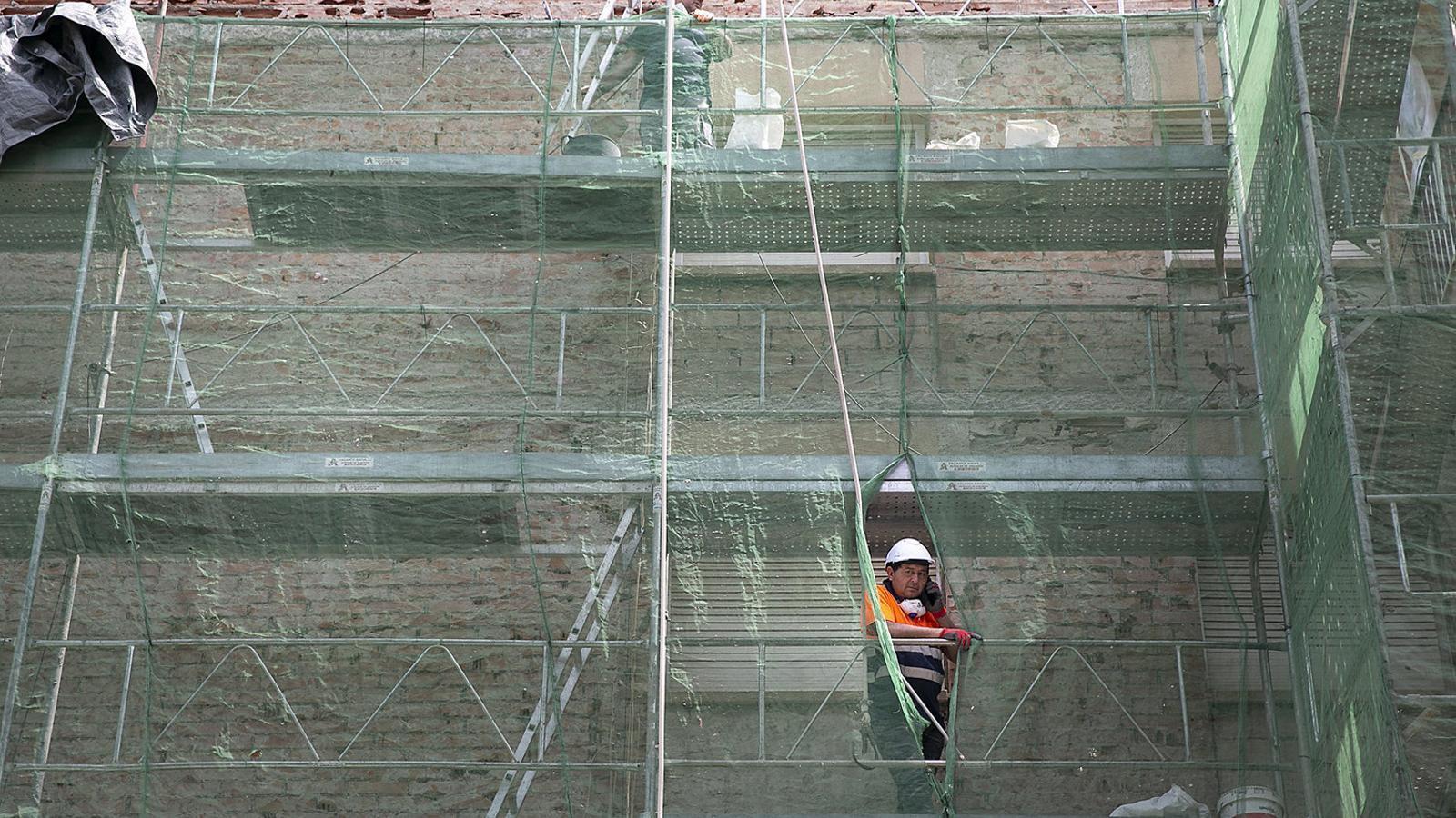 Un empleat de la construcció treballa a la bastida d'un edifici a Cerdanyola del Vallès.