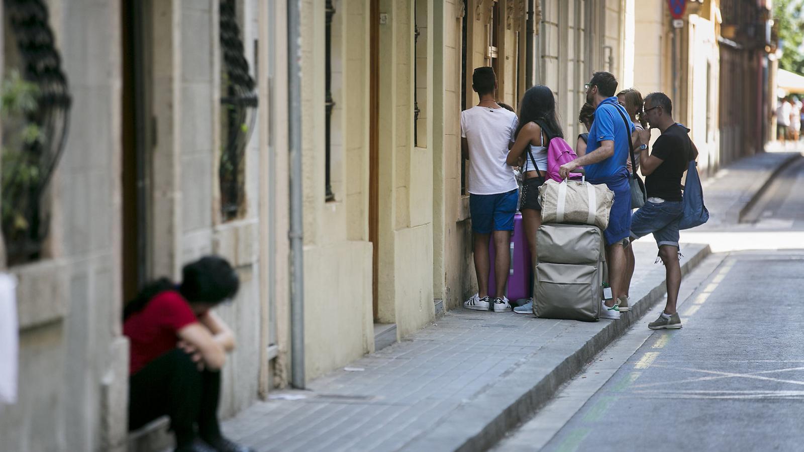 Un grup de turistes entrant en un apartament turístic al barri de la Barceloneta.