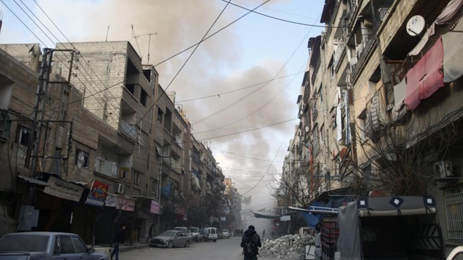 Un home camina pels carrers de Douma, a Guta de l'est, amb la columna de fum dels bombardejos al fons.